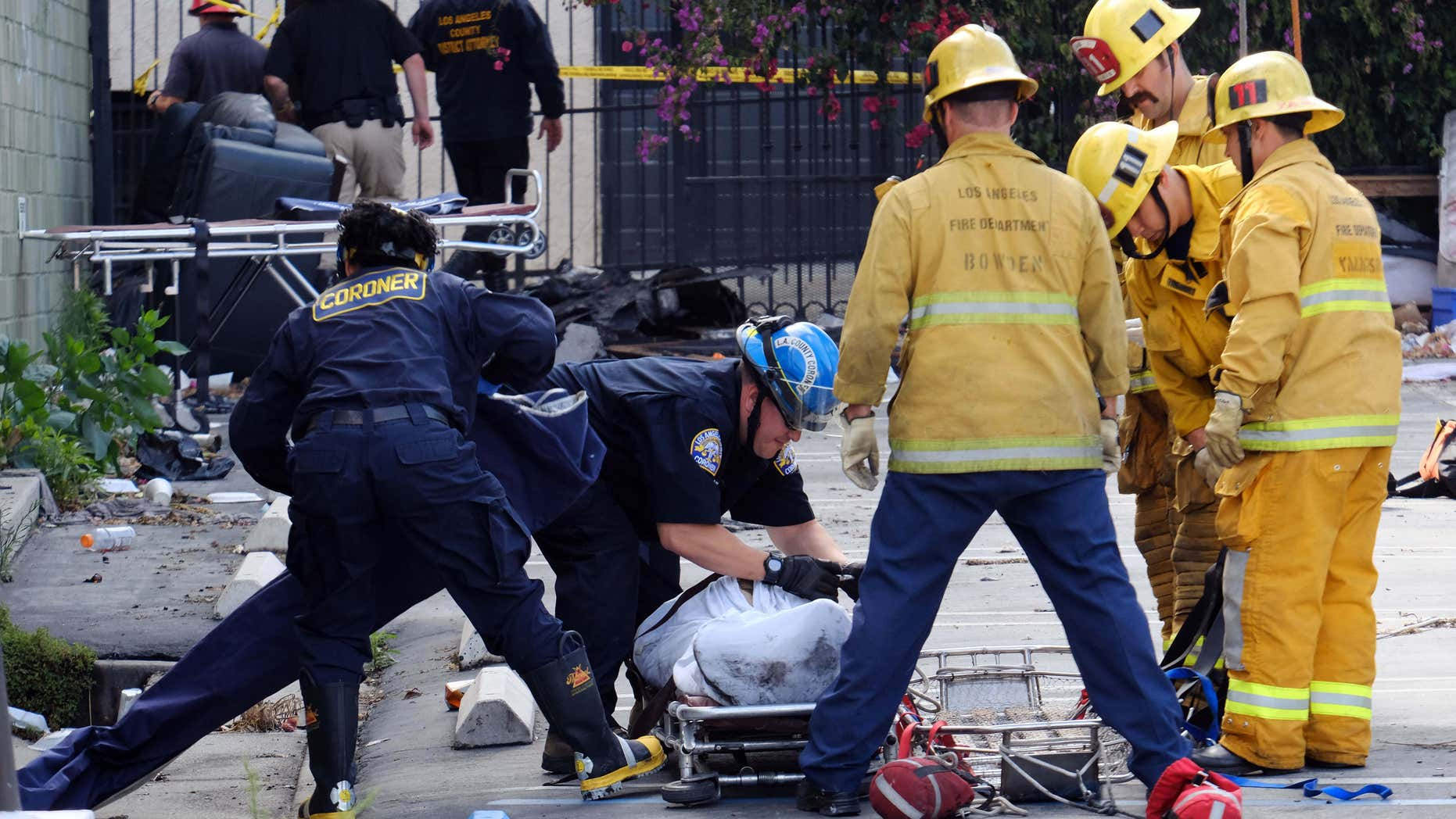 June 14, 2016: Coroner's officials and firefighters prepare to move one of four bodies found in the burned-out ruins of a abandoned office building in the Westlake district just west of downtown Los Angeles.