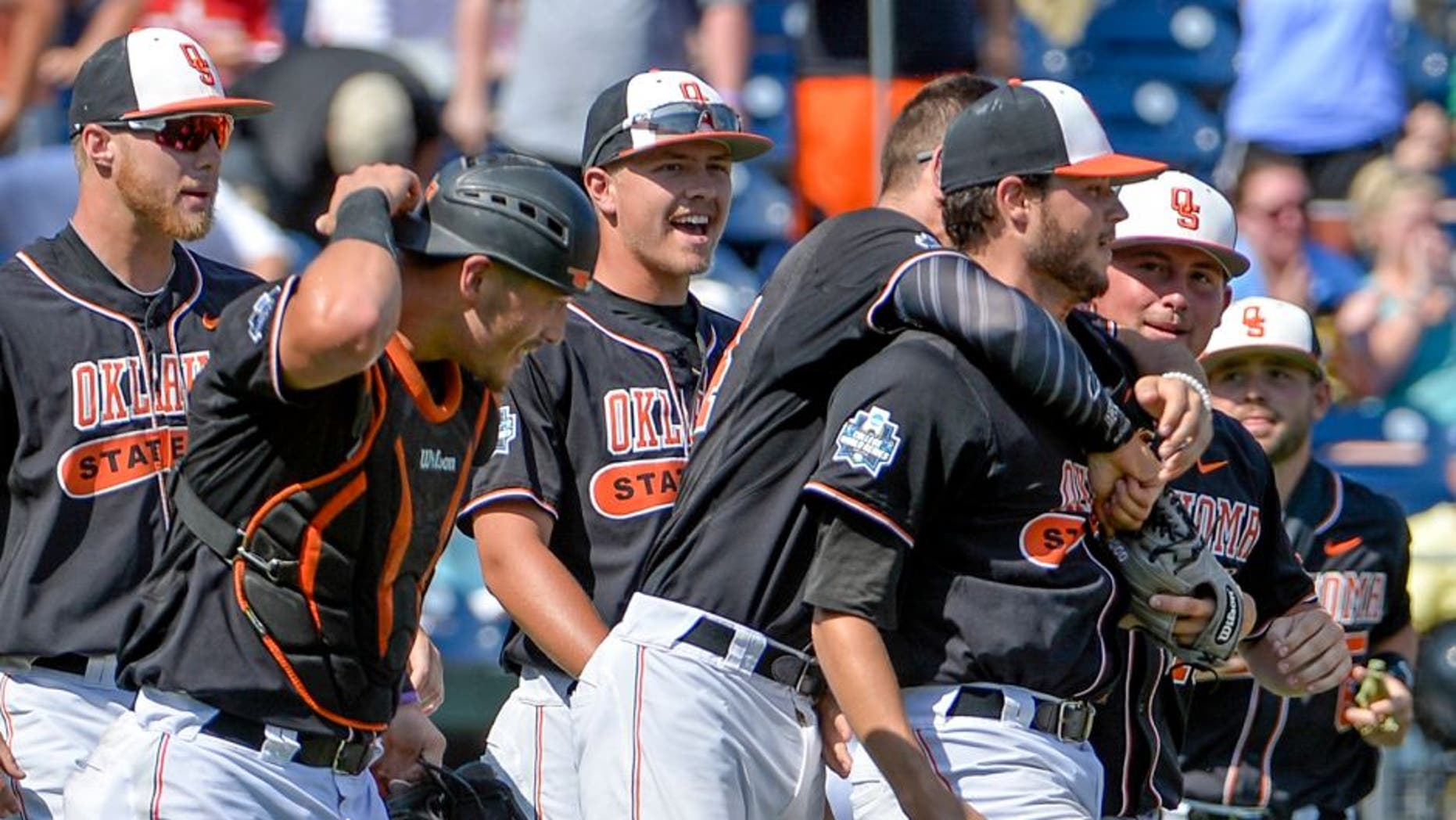 Oklahoma State starting pitcher Thomas Hatch, third from right, is congratulated by teammates after the last out of an NCAA men's College World Series baseball game against UC Santa Barbara in Omaha, Neb., Saturday, June 18, 2016. (AP Photo/Mike Theiler)