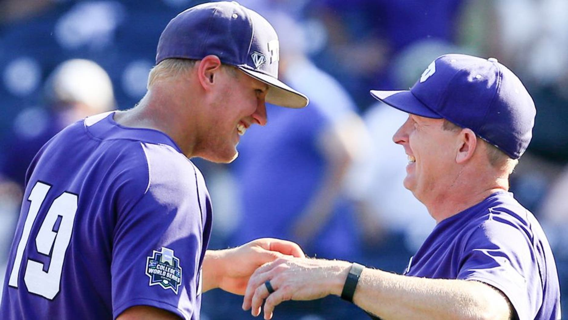 TCU's Luken Baker, left, celebrates with coach Jim Schlossnagle, right, following an NCAA men's College World Series baseball game against Texas Tech in Omaha, Neb., Sunday, June 19, 2016. Baker hit a go-ahead three-run home run in the top of the ninth and TCU won 5-3. (AP Photo/Nati Harnik)
