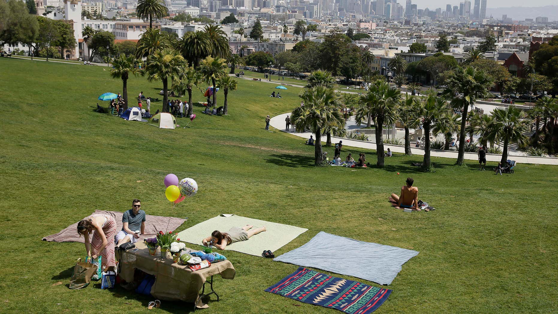 May 28, 2016: A group spreads out blankets for a party at Dolores Park in San Francisco.