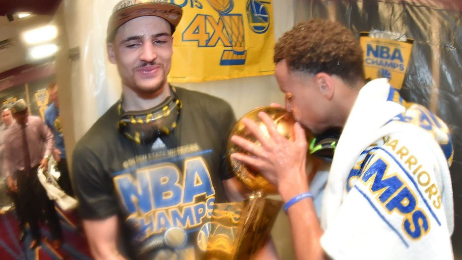 CLEVELAND, OH - JUNE 16: Klay Thompson #11 and Stephen Curry #30 of the Golden State Warriors celebrate with the Larry O'Brien Championship Trophy in the locker room after a victory over the Cleveland Cavaliers in Game Six to win the 2015 NBA Finals at The Quicken Loans Arena on June 16, 2015 in Cleveland, Ohio. NOTE TO USER: User expressly acknowledges and agrees that, by downloading and/or using this Photograph, user is consenting to the terms and conditions of the Getty Images License Agreement. Mandatory Copyright Notice: Copyright 2015 NBAE (Photo by Andrew D. Bernstein/NBAE via Getty Images)