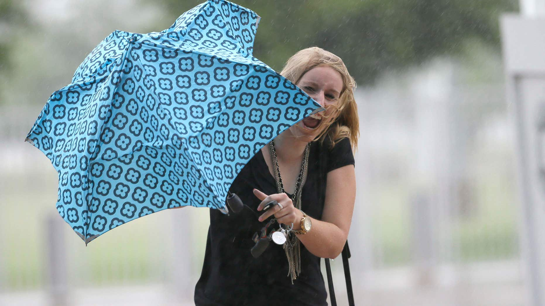 June 17, 2015: Betsy Lauritzen reacts after she was caught off guard by a strong gust of wind caused by Tropical Depression Bill in Arlington, Texas.