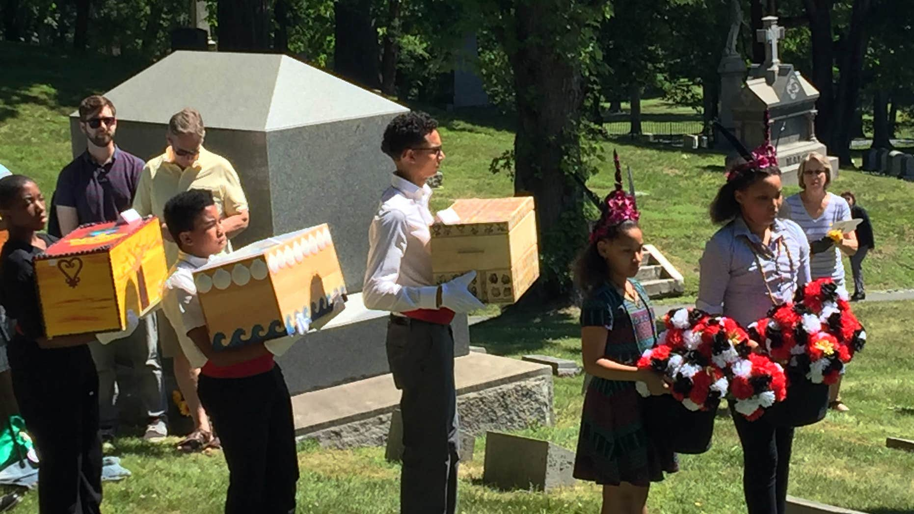June 18, 2016: In this photo provided by the Albany Diocesan Cemeteries, pallbearers carry the remains of 14 slaves to awaiting graves at St. Agnes Cemetery in Albany, N.Y.