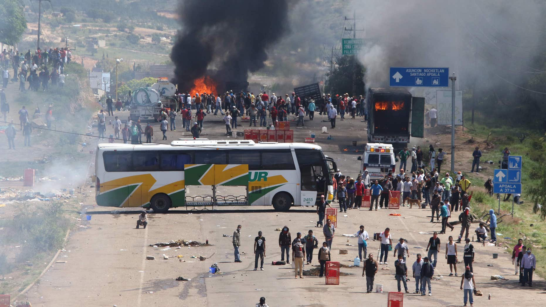 June 19, 2016: Protesting teachers who were blocking a federal highway hold their positions with a passenger bus across the road and burning trucks as they battle with riot police in the state of Oaxaca, near the town of Nochixtlan, Mexico.