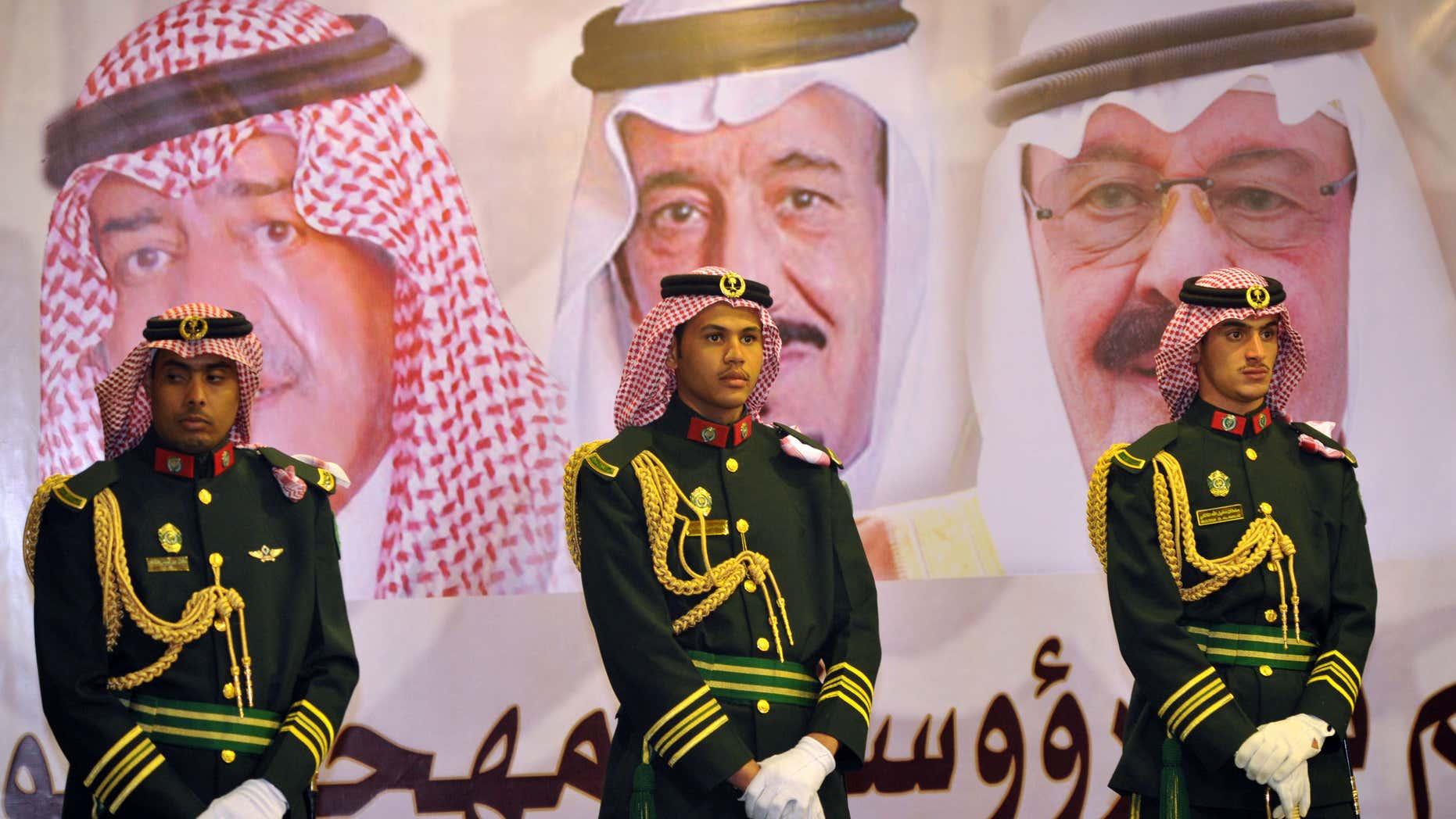 Feb. 18, 2014: Saudi royal guards stand on duty in front of portraits of King Abdullah bin Abdulaziz, right, then Crown Prince Salman bin Abdulaziz, center, and Muqrin bin Abdulaziz during a culture festival in Riyadh, Saudi Arabia.