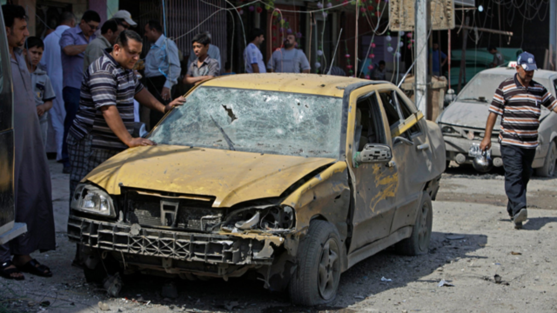 June 20: People inspect at the scene a car bomb attack in Baghdad, Iraq.