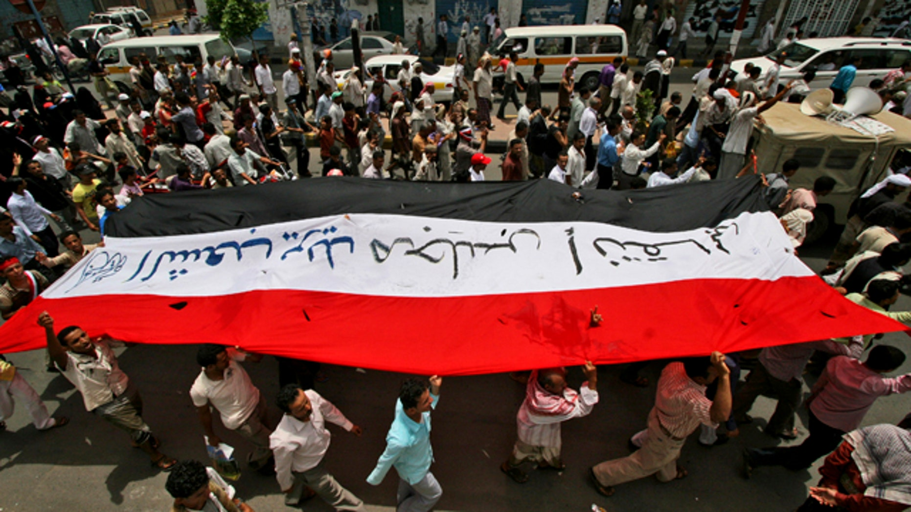June 20: Anti-government protestors hold up their national flag during a demonstration demanding the resignation of Yemeni President Ali Abdullah Saleh, in Taiz, Yemen.