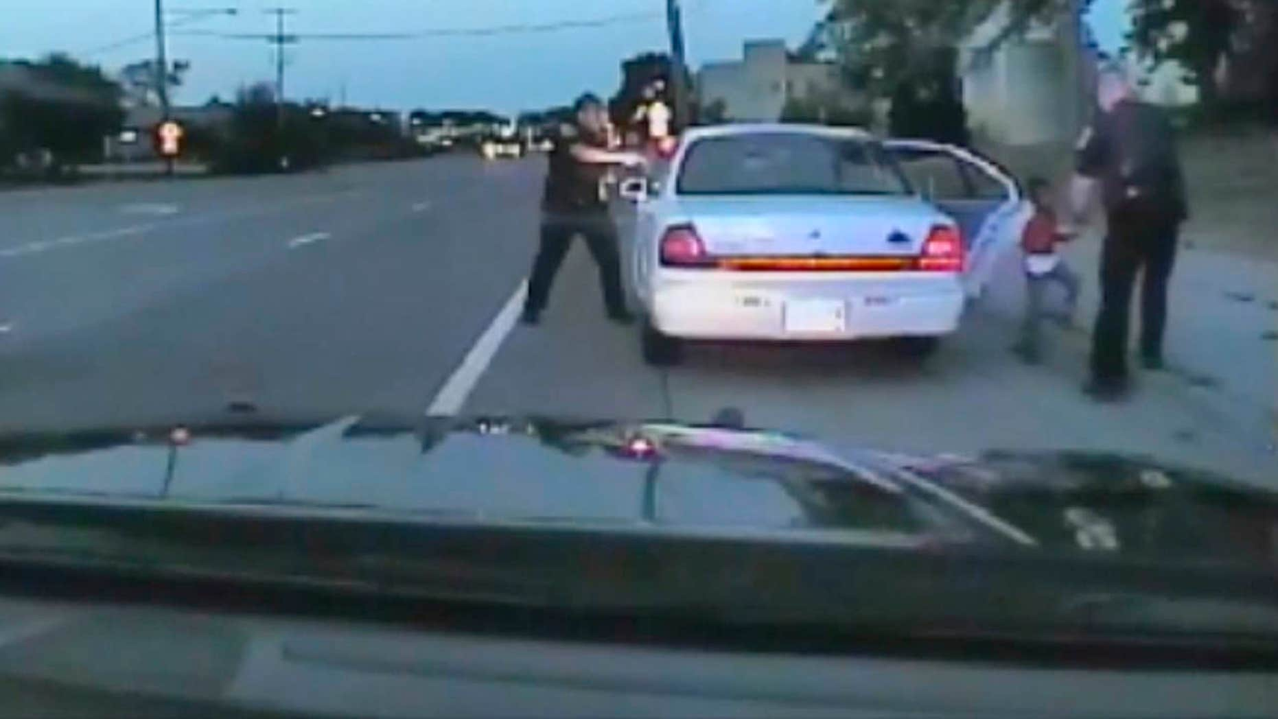 In this image made from July 6, 2016, video captured by a camera in the squad car of St. Anthony Police officer Jeronimo Yanez, the Minnesota police officer is shown after shooting into the vehicle at Philando Castile during a traffic stop in Falcon Heights, Minn., as the 4-year-old daughter of Castile's girlfriend, Diamond Reynolds, starts to get out of the car and is grabbed by an officer.