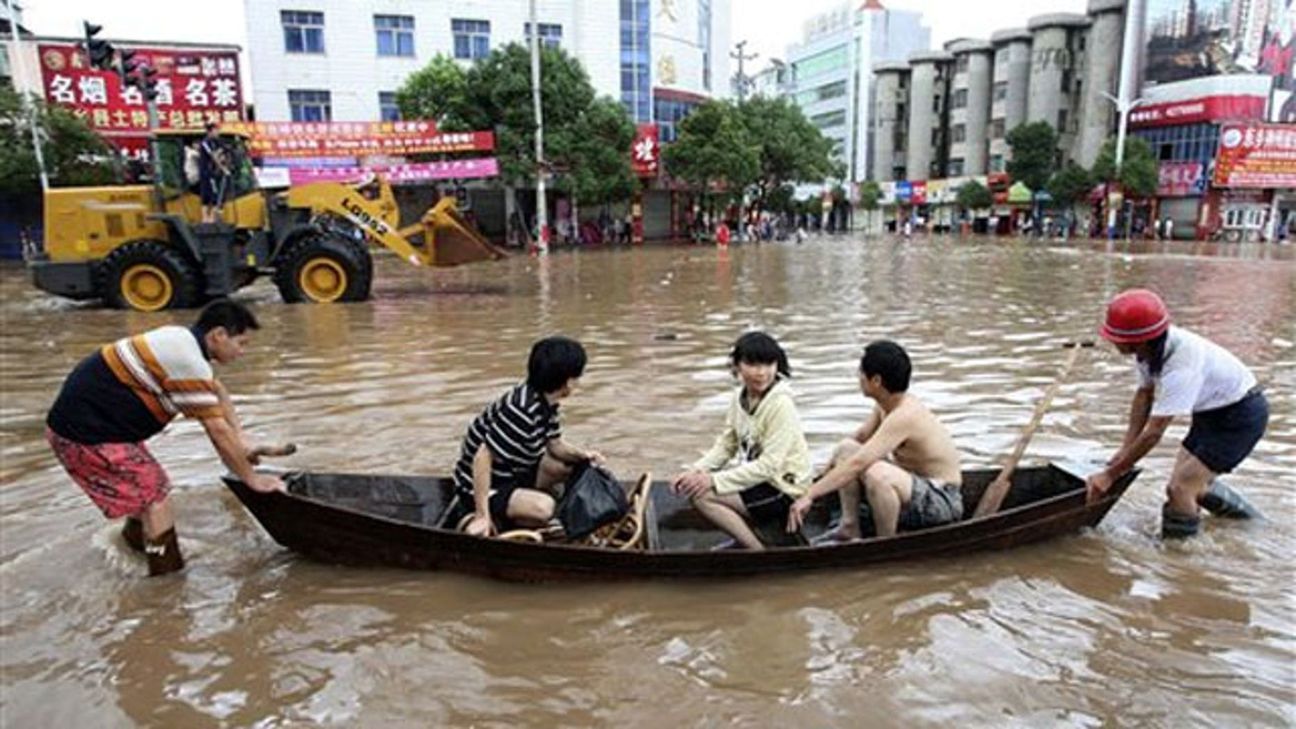 June 20: Chinese residents cross a flooded street with the help of a wooden boat in Dongxiang county in China's Jiangxi province.