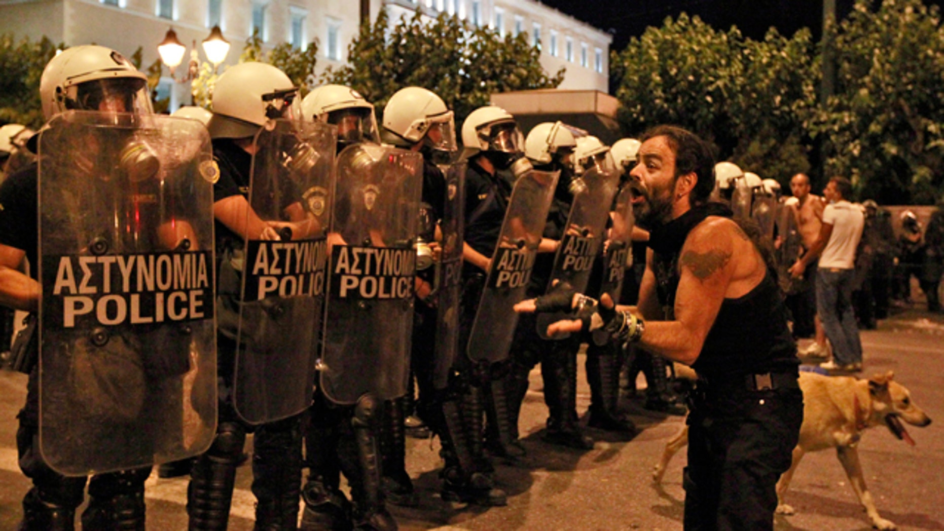 June 22: A lone protester challenges Greek riot police officers at Syntagma square in front of the Greek Parliament in central Athens, during minor scuffles following a peaceful ongoing rally against plans for new austerity measures.