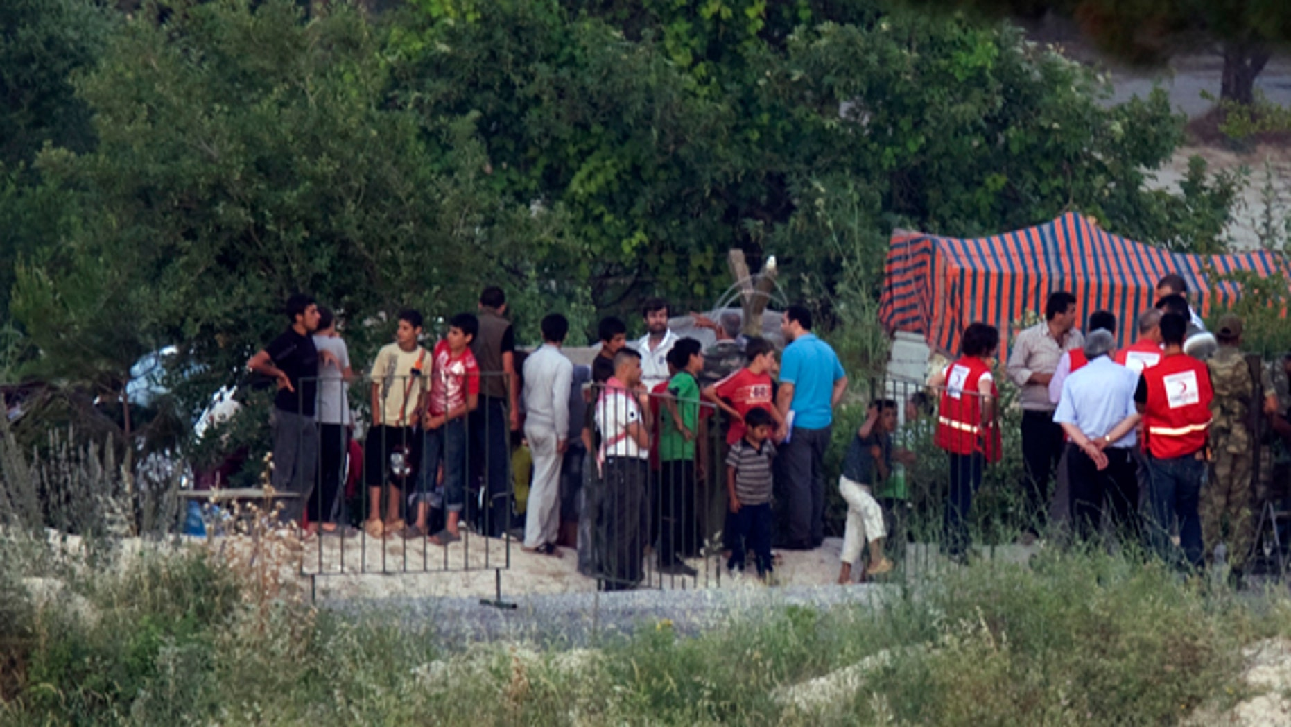 June 22: Officials of Turkey's Red Cresdent distribute free food to Syrians waiting in Syria alongside Turkey-Syria border near the Turkish village of Guvecci in Hatay province, Turkey.