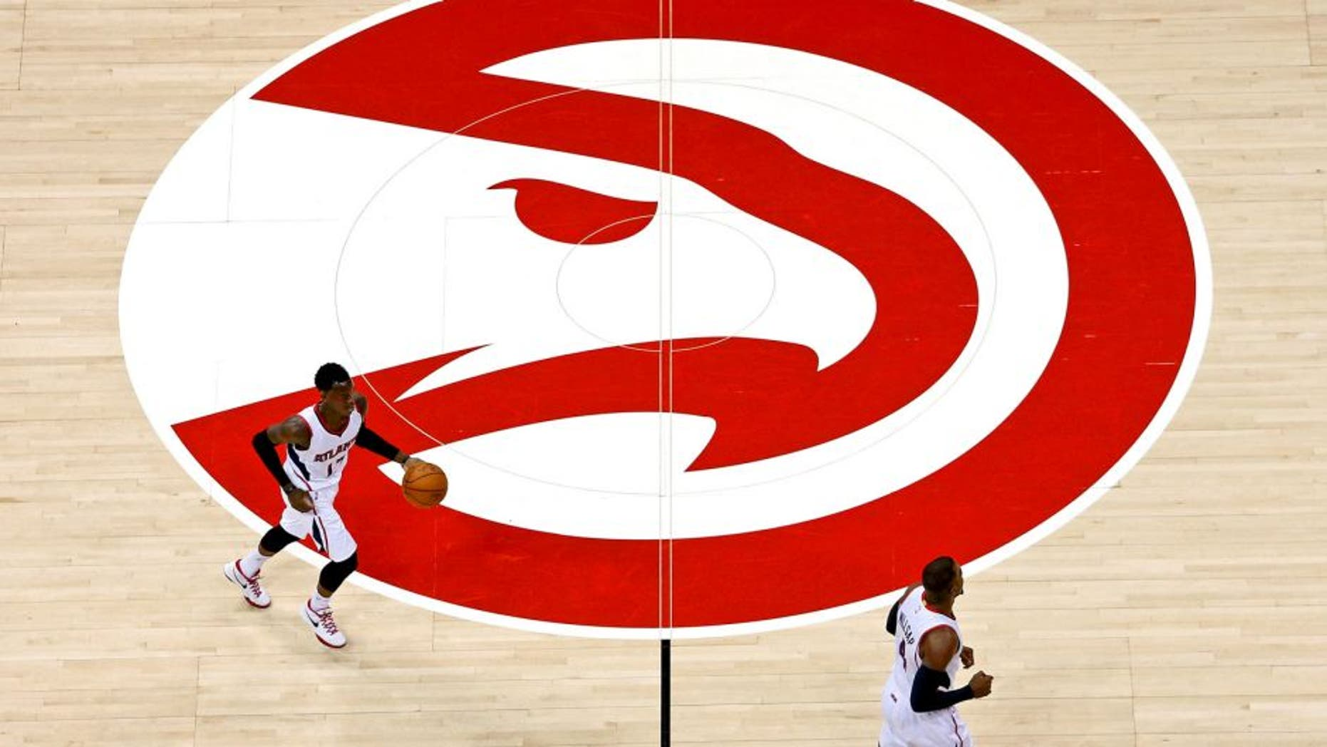 Mar 27, 2015; Atlanta, GA, USA; Atlanta Hawks guard Dennis Schroder (17) and forward Paul Millsap (4) cross the Atlanta Hawks logo in the first quarter of their game against the Miami Heat at Philips Arena. Mandatory Credit: Jason Getz-USA TODAY Sports