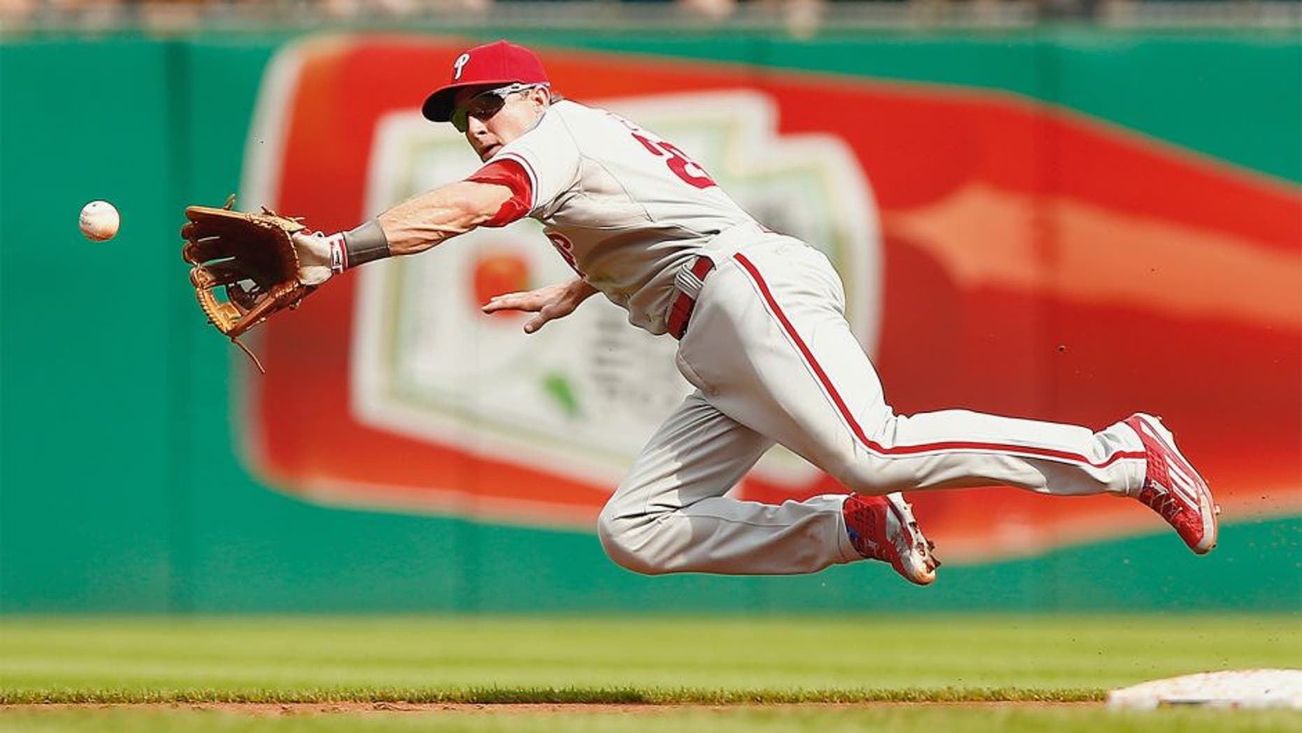 PITTSBURGH, PA - JUNE 13: Chase Utley #26 of the Philadelphia Phillies fields a ground ball while midair in the second inning against the Pittsburgh Pirates during the game at PNC Park on June 13, 2015 in Pittsburgh, Pennsylvania. (Photo by Jared Wickerham/Getty Images)