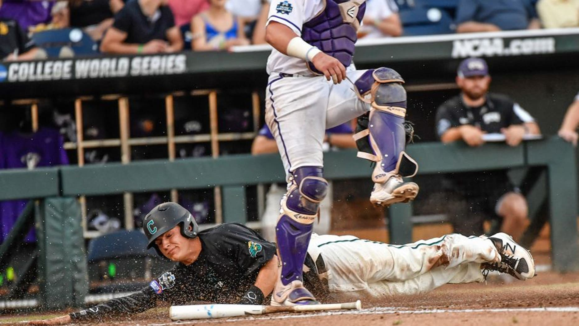 Coastal Carolina's Anthony Marks, bottom, scores behind TCU catcher Evan Skoug on a bunt by Billy Cooke during the third inning of an NCAA College World Series baseball game in Omaha, Neb., Friday, June 24, 2016. (AP Photo/Ted Kirk)