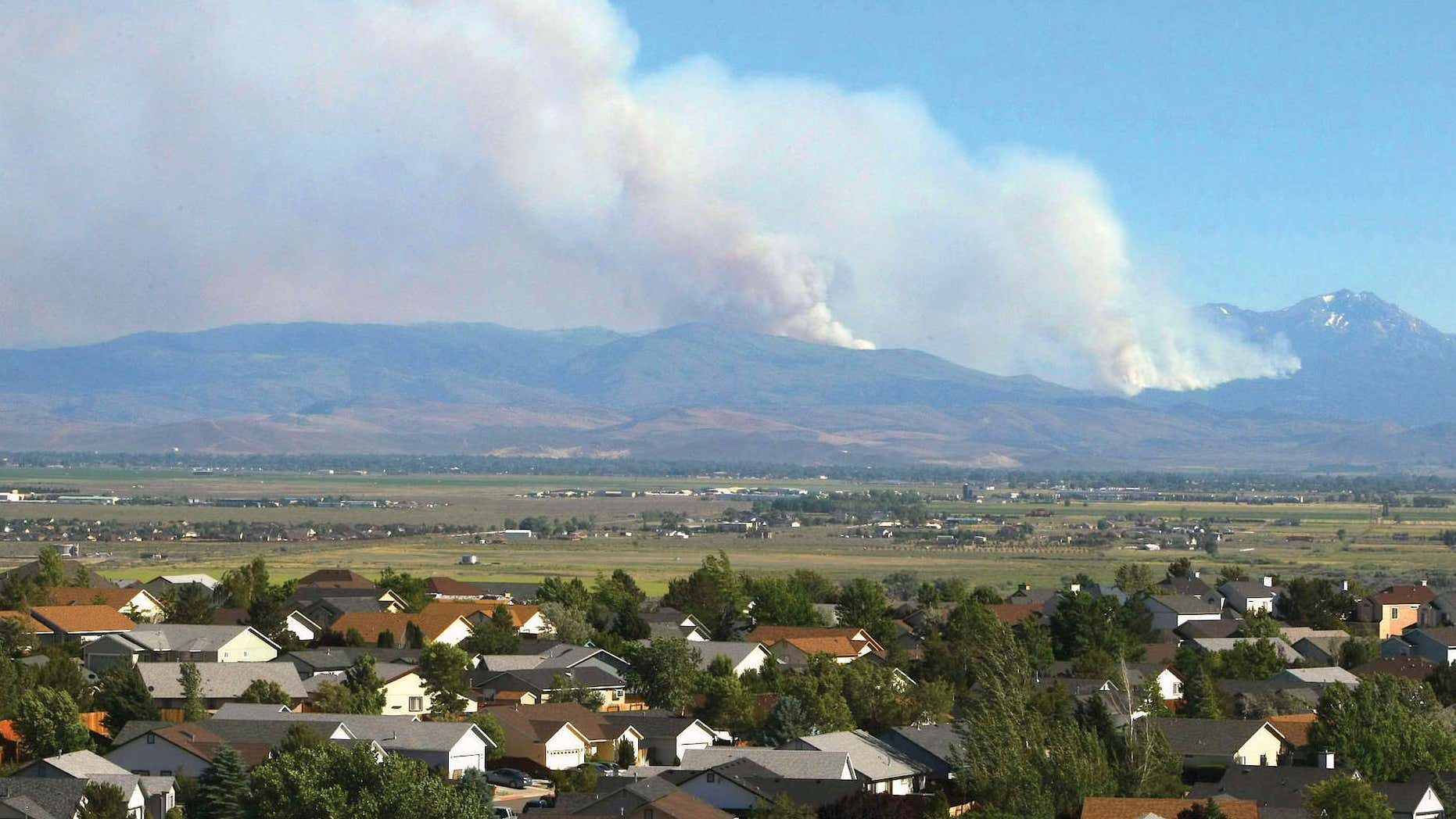 June 22, 2015: Smoke from the Washington Fire rises over the mountains in Markleeville, Calif.