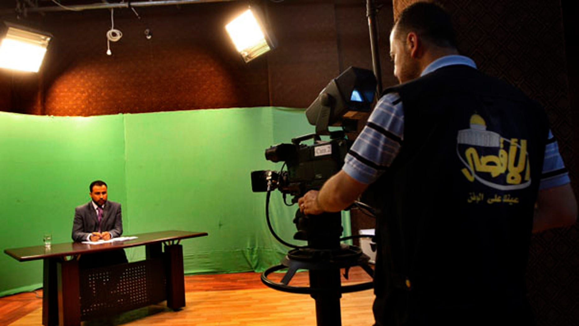 June 15: A Palestinian cameraman films a broadcaster presenting a live program at the Hamas Al Aqsa TV station in Gaza City.