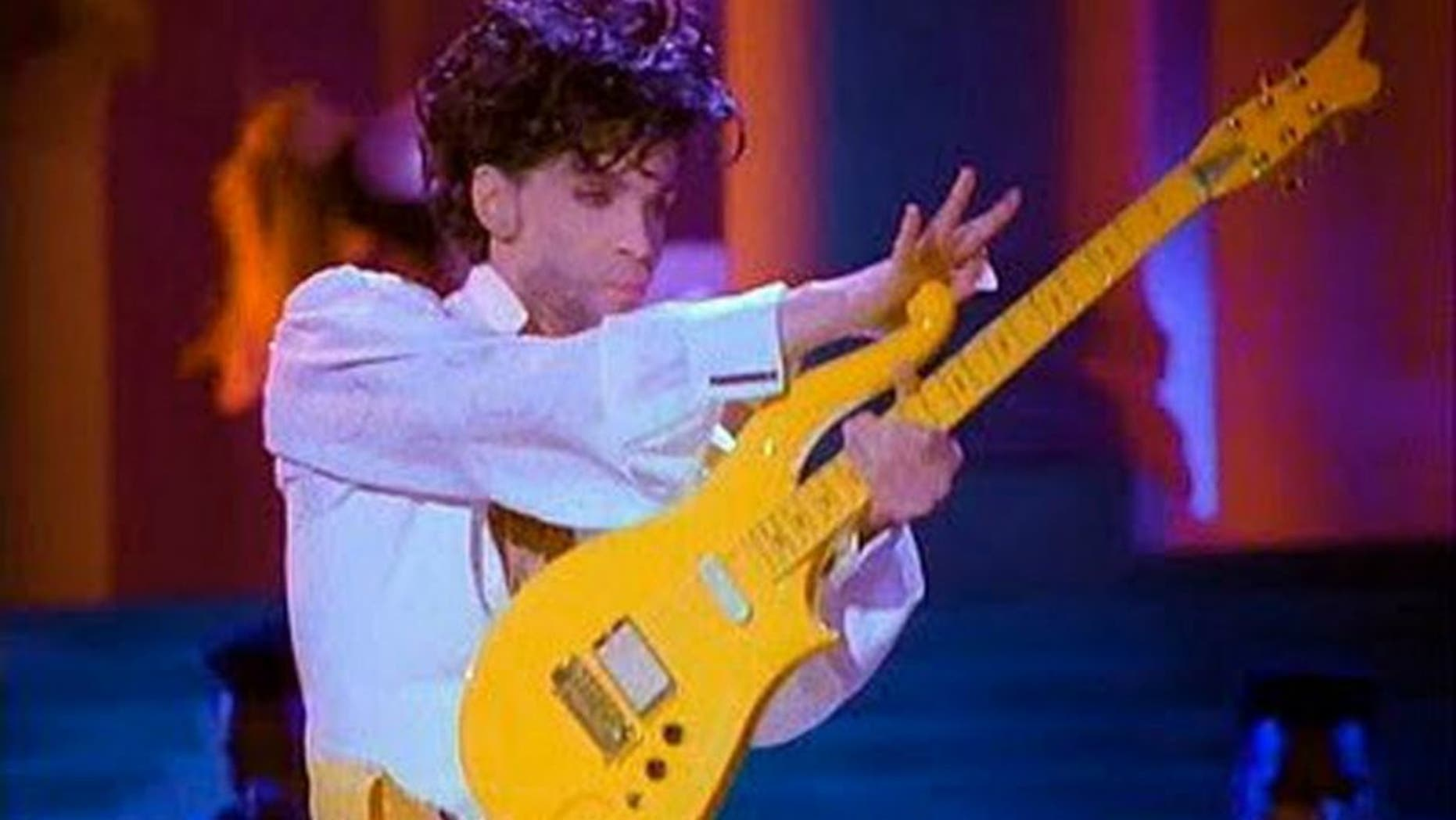This photo provided by Heritage Auctions shows Prince playing his Yellow Cloud electric guitar. Indianapolis Colts owner Jim Irsay has purchased the Yellow Cloud electric guitar that Prince used in numerous concerts until the mid-1990's. The NFL football team owner and collector of musical instruments paid $137,500 for the guitar at an auction in Beverly Hills Saturday, June 25, 2016. Heritage Auctions, which conducted the auction, says the solid body guitar was a favorite of the late musician from the late 1980's to the mid-1990's. (Heritage Auctions via AP)
