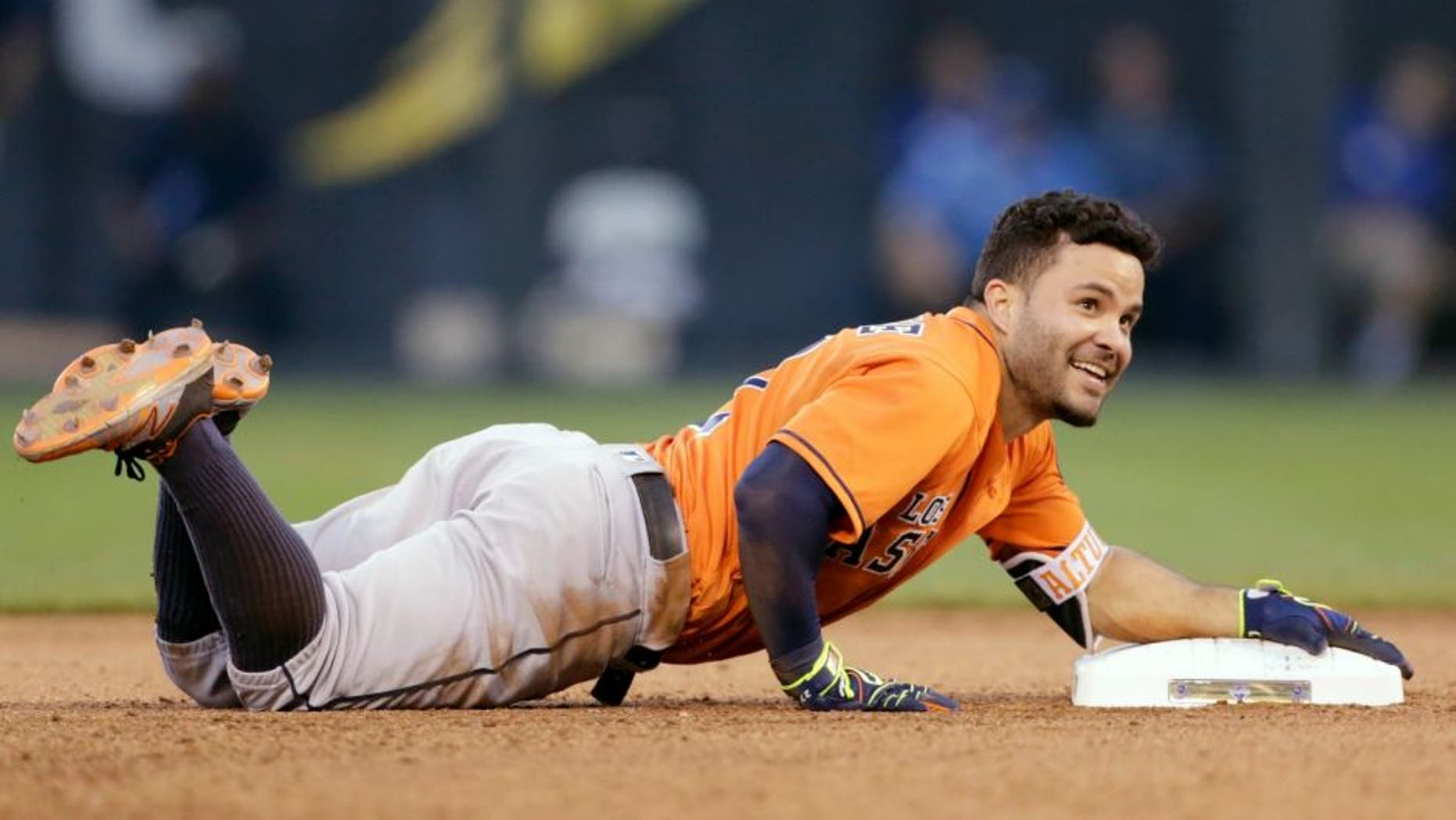 Houston Astros Jose Altuve reacts after tripping over second base while attempting a triple after a hit in the sixth inning of a baseball game against the Kansas City Royals at Kauffman Stadium in Kansas City, Mo., Saturday, June 25, 2016. The Astros beat the Royals 13-5. (AP Photo/Colin E. Braley)