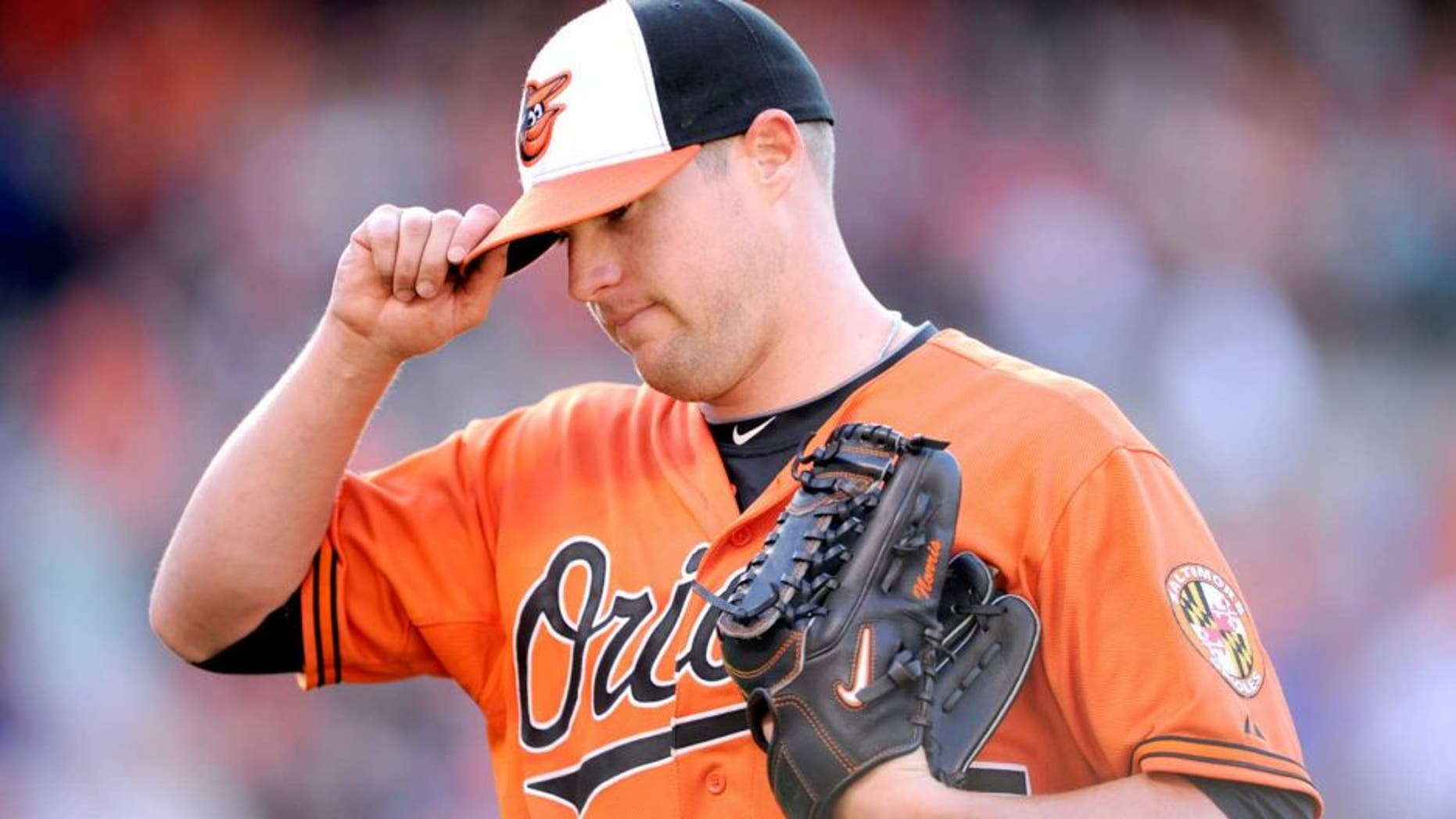 Baltimore Orioles starting pitcher Bud Norris touches the brim of his hat as he walks back to the dugout after he was pulled from the baseball game against the Toronto Blue Jays during the seventh inning Saturday, June 14, 2014, in Baltimore. The Orioles won 3-2. (AP Photo/Nick Wass)