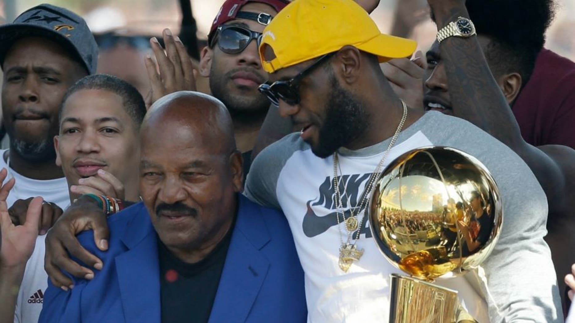 Former Cleveland Brown' Jim Brown, left, passes the Larry O'Brien NBA Championship Trophy to LeBron James during a rally, Wednesday, June 22, 2016, in Cleveland. The Cavaliers made history by overcoming a 3-1 deficit to beat the Golden State Warriors in the NBA Finals and end the city's 52-year drought without a professional sports championship. (AP Photo/Tony Dejak)