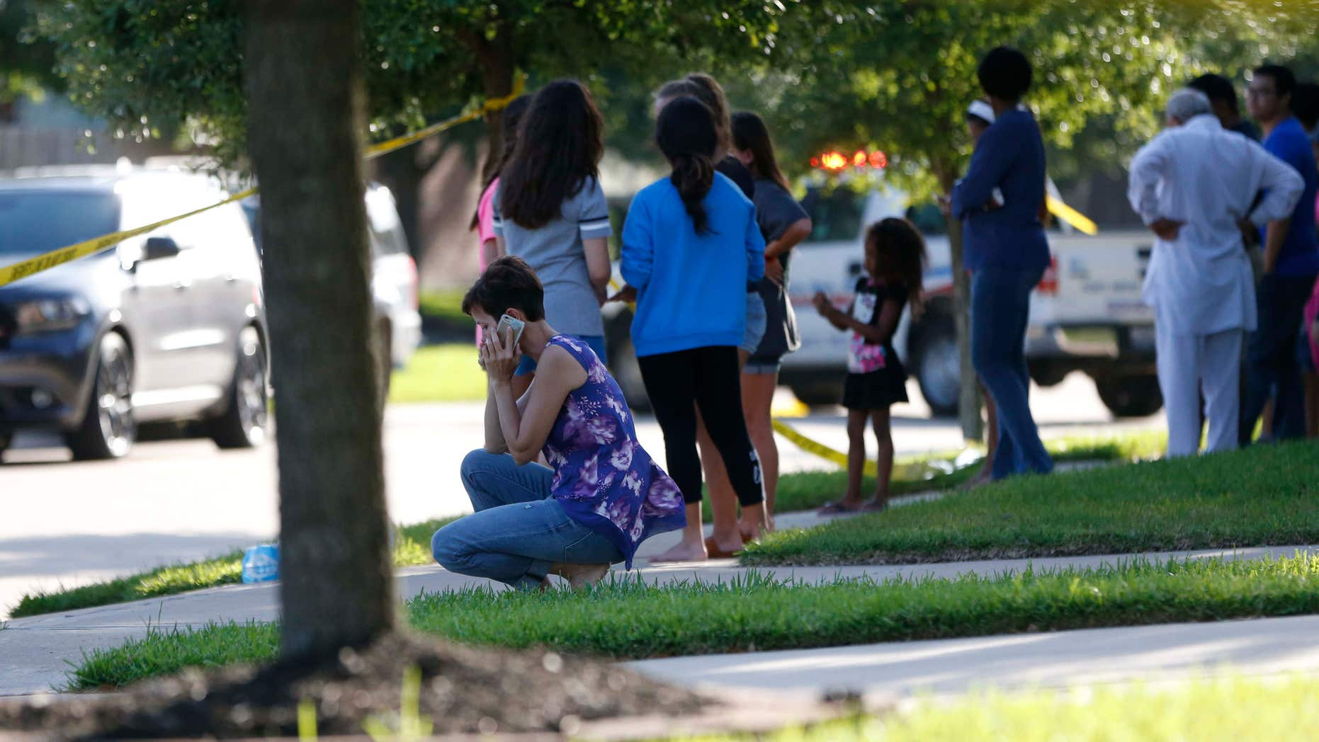 In this Friday, June 24, 2016 photo, neighbors gather to watch as Fort Bend County Sheriffs department investigates a shooting at Blanchard Grove and Remson Hollow in Katy, Texas.