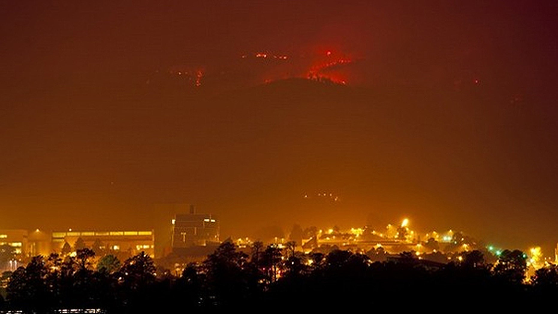 June 27: Flames from the Las Conchas fire burn in the hills above Los Alamos National Laboratory, a nuclear facility.