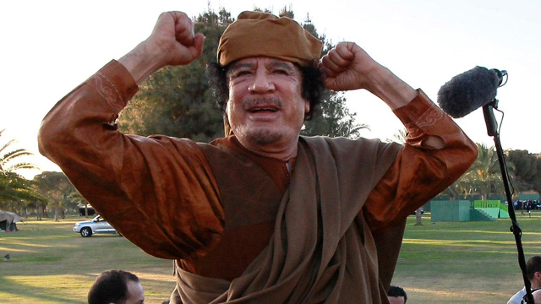 April 10: Libyan leader Muammar al-Qaddafi gestures to his supporters in Tripoli, Libya.