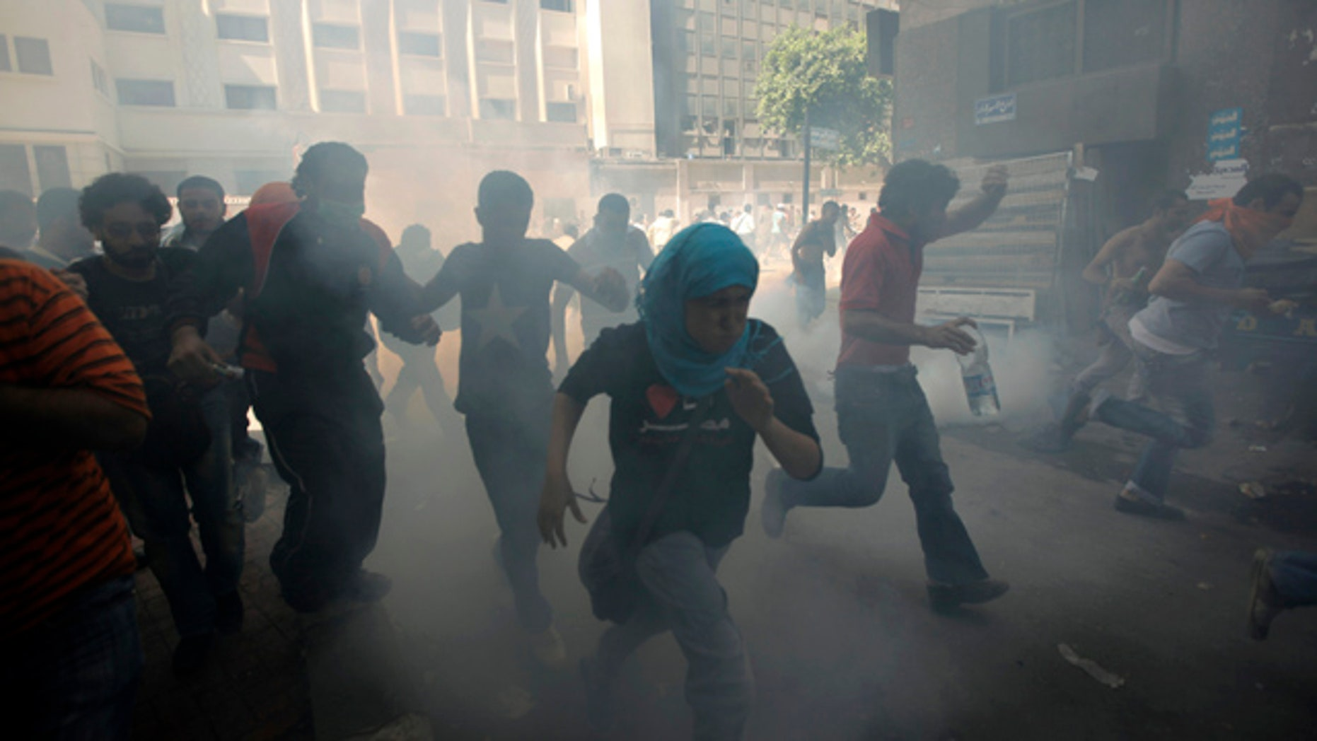 June 29: Egyptian protesters run to avoid tear gas during clashes with security forces at Tahrir Square in Cairo, Egypt.