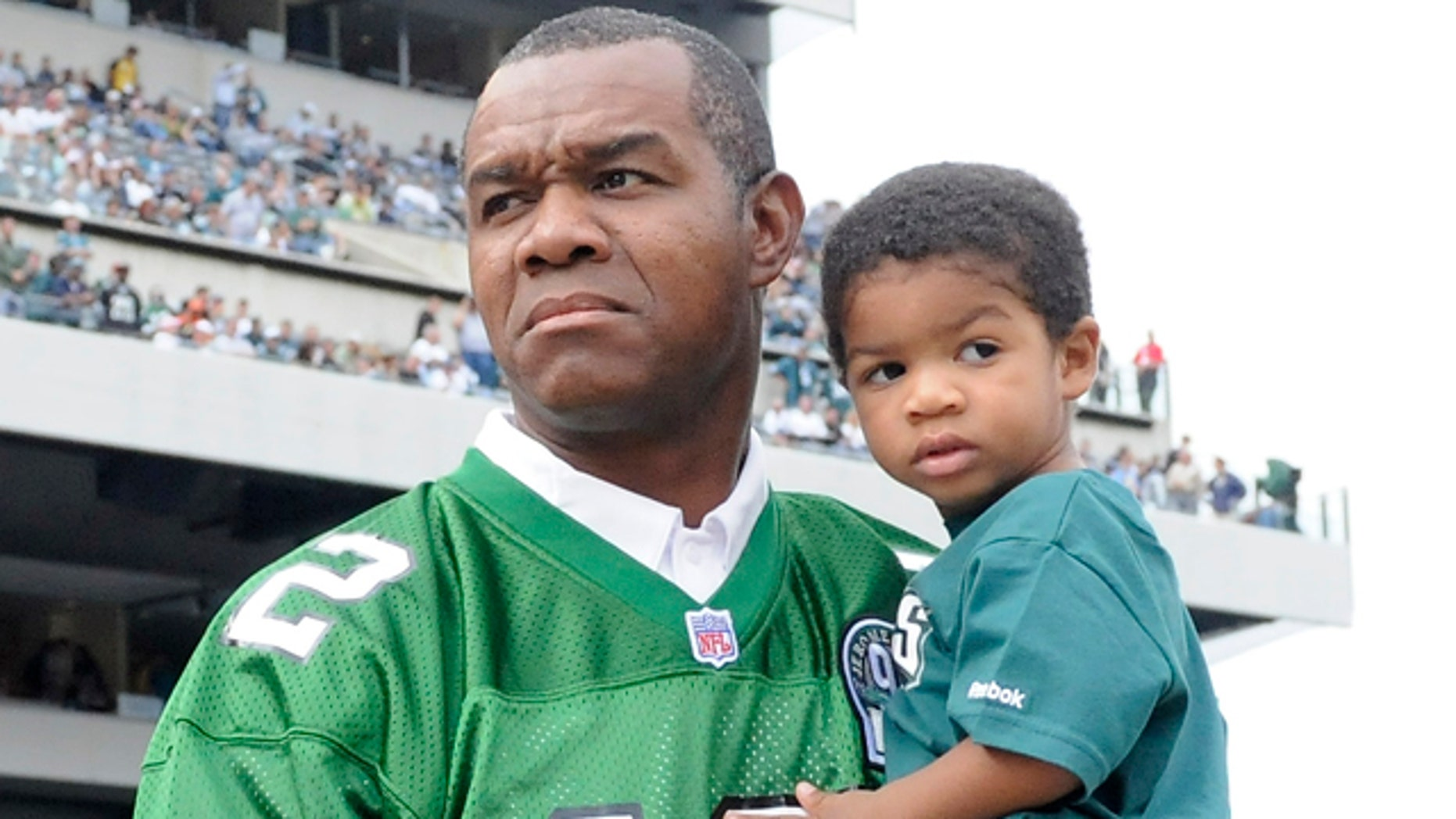 This photo made Sept. 27, 2009, shows former Philadelphia Eagles football player Randall Cunningham holding his son, Christian, during halftime of an NFL football game, in Philadelphia.
