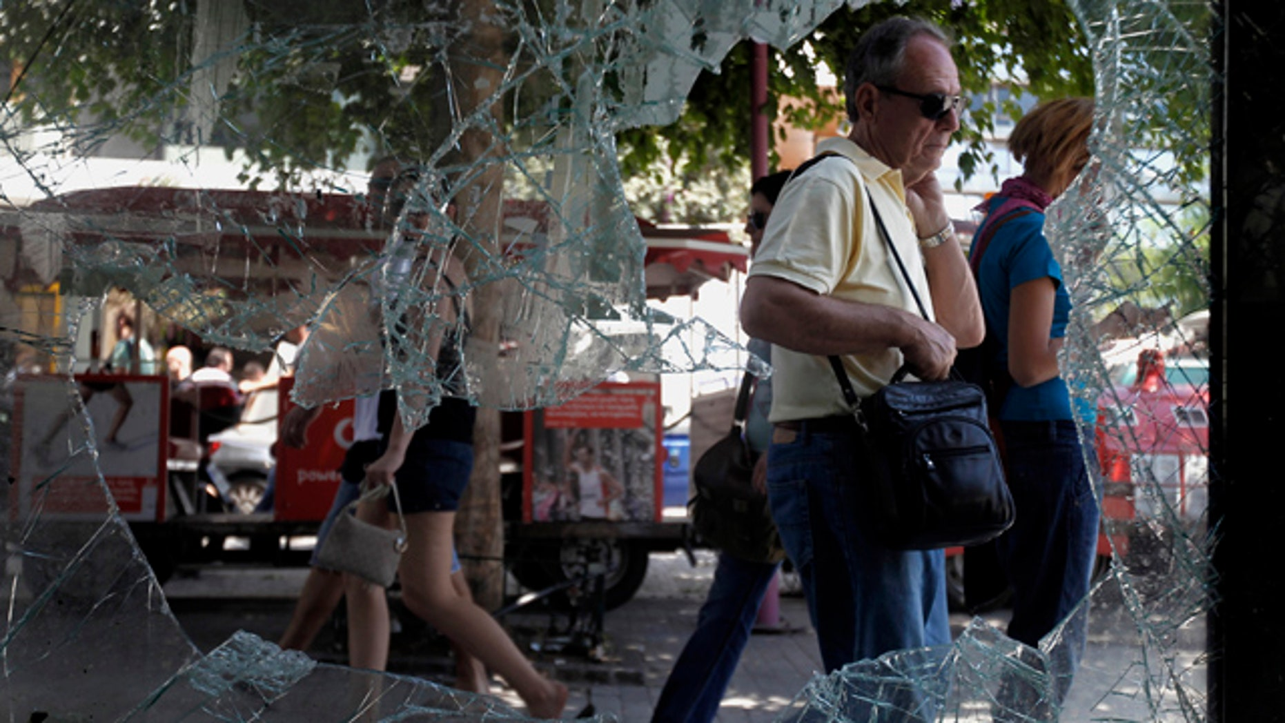June 30: Athenians walk by a broken window of a building in central Athens.
