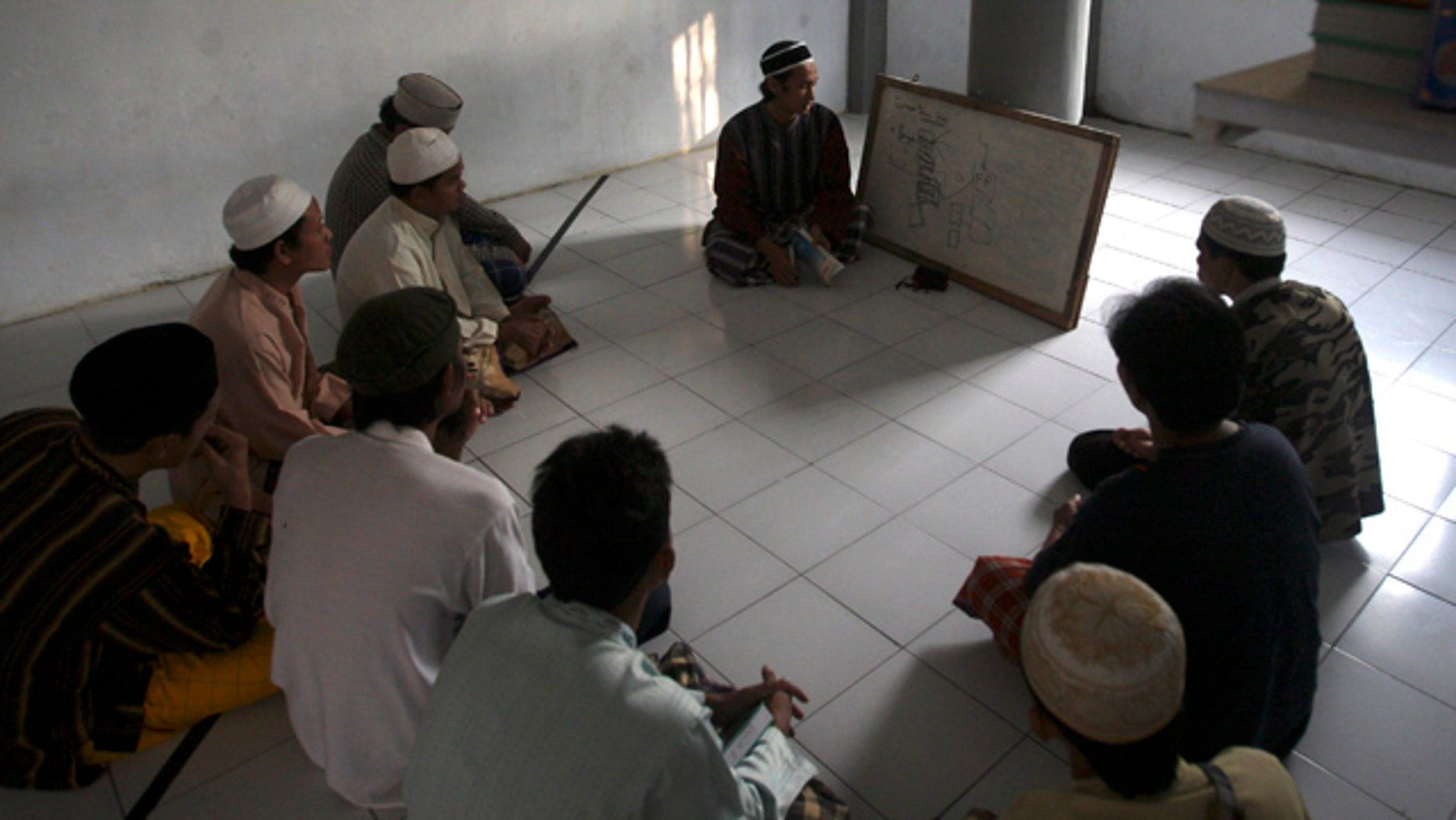 """June 6: Prisoners attend a religious class led by a jailed militant Arif Syaifudin, also known as """"Firdaus,"""" in Block F of the Porong prison in East Java, Indonesia."""