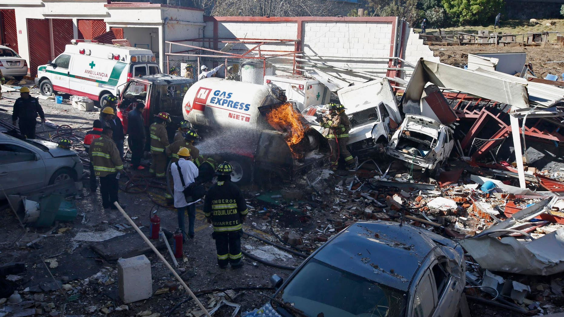 FILE - In this Jan. 29, 2015 file photo, firefighters spray water on a gas truck that caused an explosion and killed five at a maternity and children's hospital in Cuajimalpa on the outskirts of Mexico City. Mexican officials said Monday, Feb. 16, 2015 that two worn-out bolts on the gas tanker truck caused a leak that resulted in the explosion. Experts said wire and Teflon tape had been improperly used on parts of the truck's valves, and Mexico City chief prosecutor Rodolfo Rios said one of the bolts was the wrong size, and the truck's gas meter had been altered to shortchange customers. (AP Photo, File)