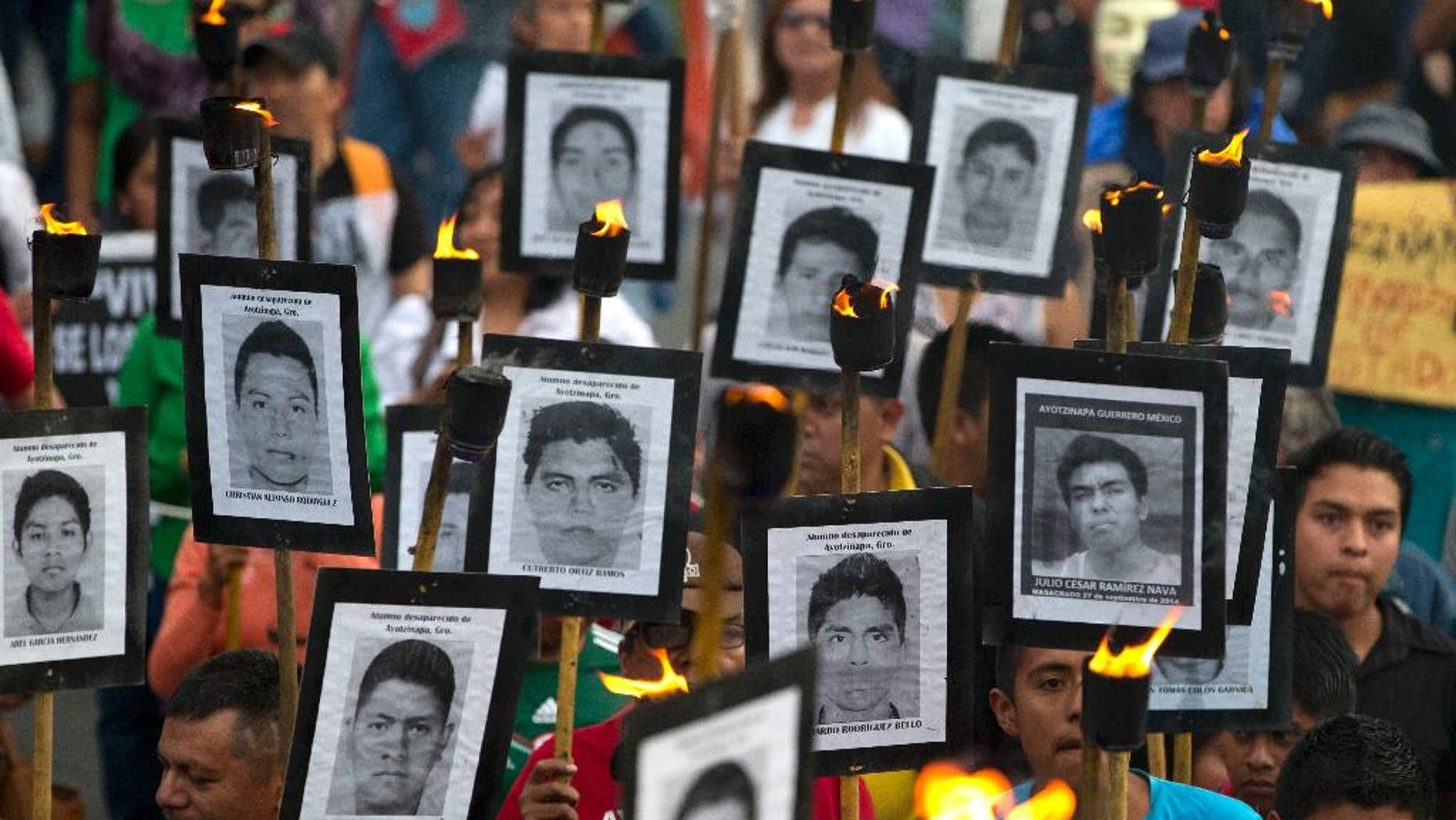 Family members of 43 missing teachers college students carry pictures of the students as they march with supporters to demand the case not be closed and that experts' recommendations about new leads be followed, in Mexico City, Tuesday, April 26, 2016. The U.N. Office of the High Commissioner for Human Rights said Tuesday that it is troubled by a group of international experts' complaints of obstacles to their investigation into Sept. 26, 2014 disappearance of the students in southern Guerrero State.(AP Photo/Rebecca Blackwell)