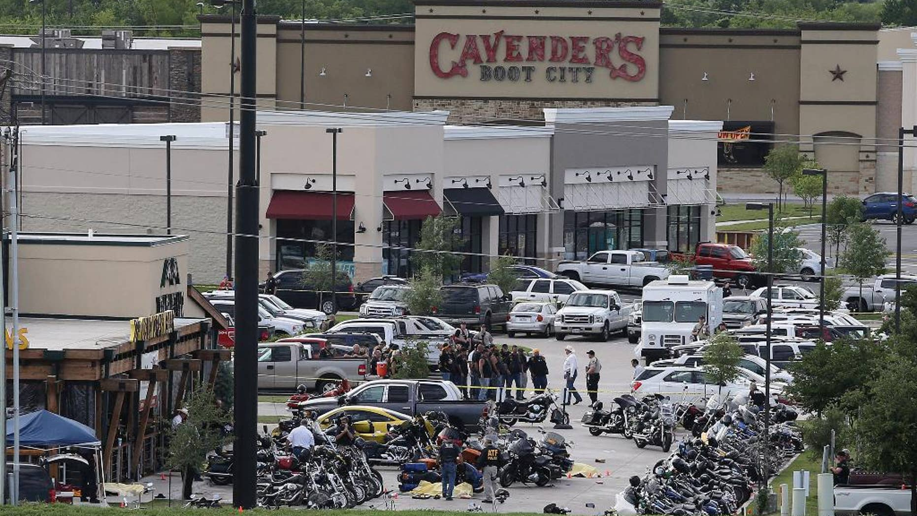 FILE - In this May 17, 2015 file photo, authorities investigate a shooting in the parking lot of Twin Peaks restaurant in Waco, Texas. The family of a biker slain in a shootout outside the Waco restaurant has sued the restaurant's parent company alleging negligence, according to a lawsuit filed Wednesday, July 8, 2015, in Dallas County.  (AP Photo/Jerry Larson, File)