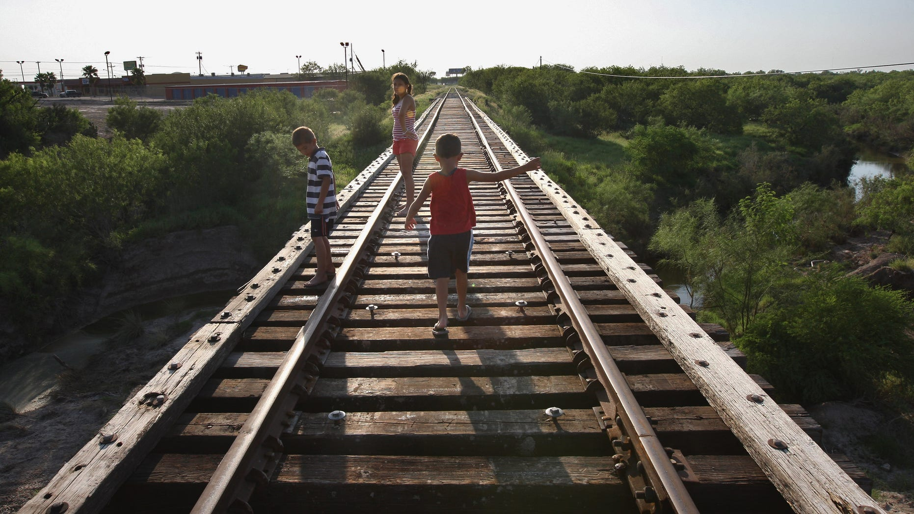RIO GRANDE CITY, TX - AUGUST 05:  Children walk across a railroad bridge August 5, 2008 in Rio Grande City, Starr County,Texas, along the border with Mexico. By many social indicators, Starr County is the poorest county in the United States. Few of its residents have full health or dental insurance and many of them must travel across the border to Mexico in order to get medical attention and buy medicine. The two-week Operation Lone Star, run by the Texas armed forces and state health officials, provided free medical care to more than 10,000 people in areas along the Texas-Mexico border.  (Photo by John Moore/Getty Images)