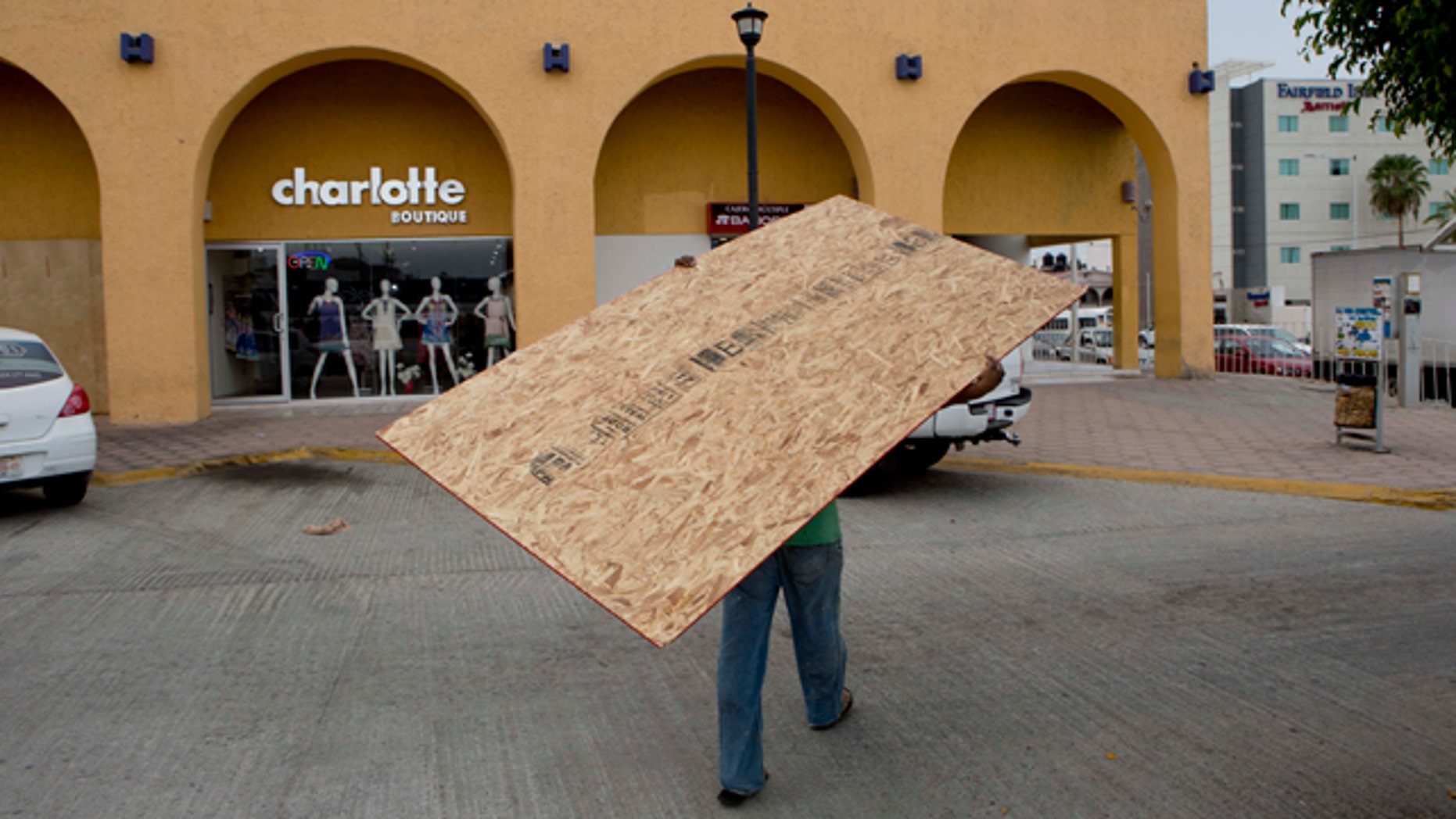 A worker hauls a board to use on a storefront window as protection against Hurricane Blanca in Cabo San Lucas, Mexico, Saturday June 6, 2015. The unpredictable Blanca, which strengthened suddenly from a Category 1 to a Category 4 storm on Saturday before weakening slightly, is expected to make landfall as a tropical storm on Monday. But authorities said its outer bands could start hitting the southern Baja California Peninsula as a hurricane on Sunday. (AP Photo/Eduardo Verdugo)