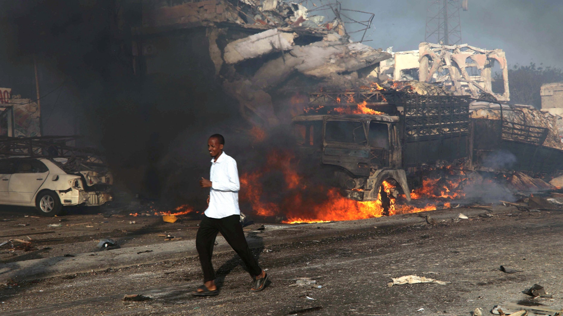FILE: A man runs past the scene of an explosion in the street in Hodan district of Mogadishu