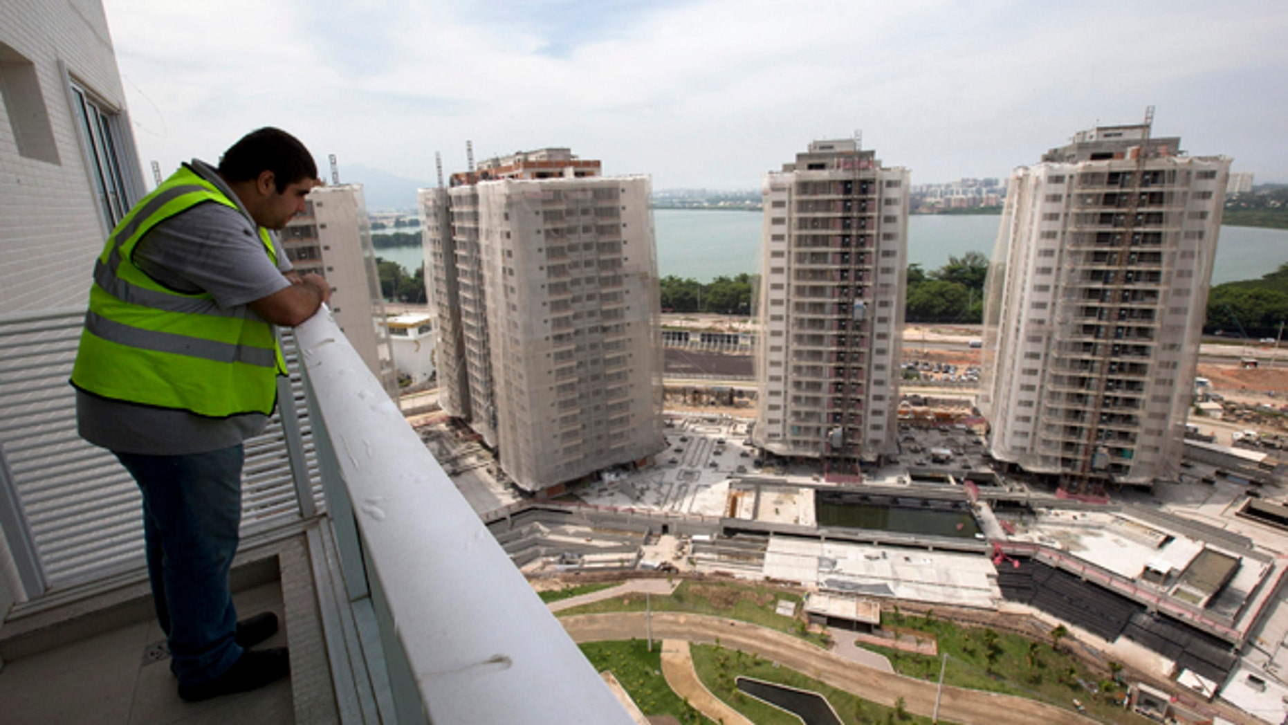 """In this March 16, 2015 photo, a worker stands on the balcony of an apartment inside the Rio 2016 Olympic Games athletes village in Rio de Janeiro, Brazil. Christopher Gaffney, who spent 5 1/2 years in Rio researching the 2014 World Cup and Olympics, called the village """"a transfer of wealth program from the public (treasury) to private construction firms."""" (AP Photo/Silvia Izquierdo)"""