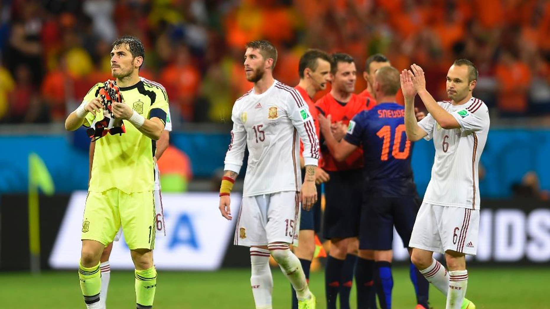 Spain's goalkeeper Iker Casillas, left, Spain's Sergio Ramos, centre and Spain's Andres Iniesta react after the group B World Cup soccer match between Spain and the Netherlands at the Arena Ponte Nova in Salvador, Brazil, Friday, June 13, 2014.  The Netherlands won the match 5-1. (AP Photo/Manu Fernandez)