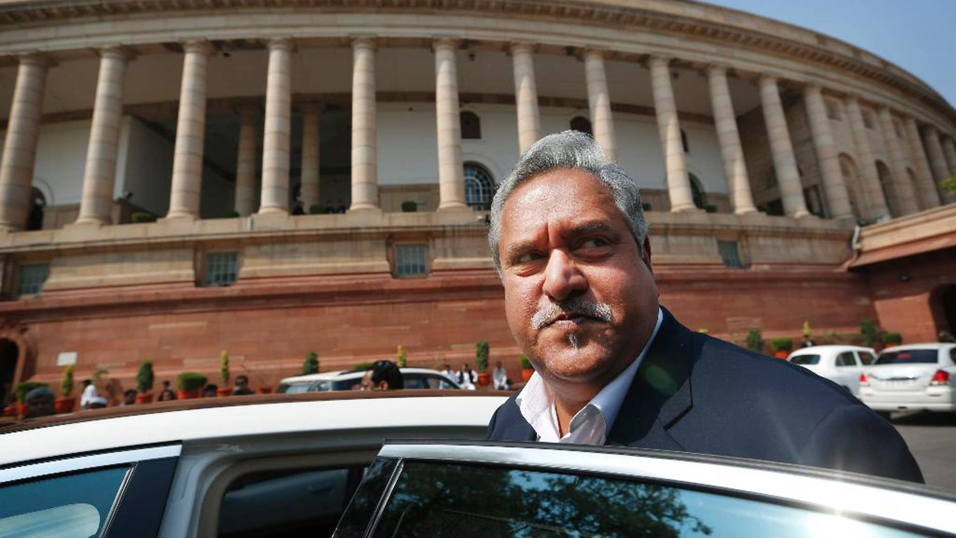 FILE- In this Feb. 27, 2013 file photo, Indian business tycoon and owner of Kingfisher Airlines Vijay Mallya gets into his car outside the Parliament in New Delhi, India. India will ask Britain to extradite Mallya to face charges of money laundering and bank demands that he pay back more than a billion dollars in loans extended to his now-defunct airline, the finance minister Arun Jaitley said Wednesday. (AP Photo/Saurabh Das, File)