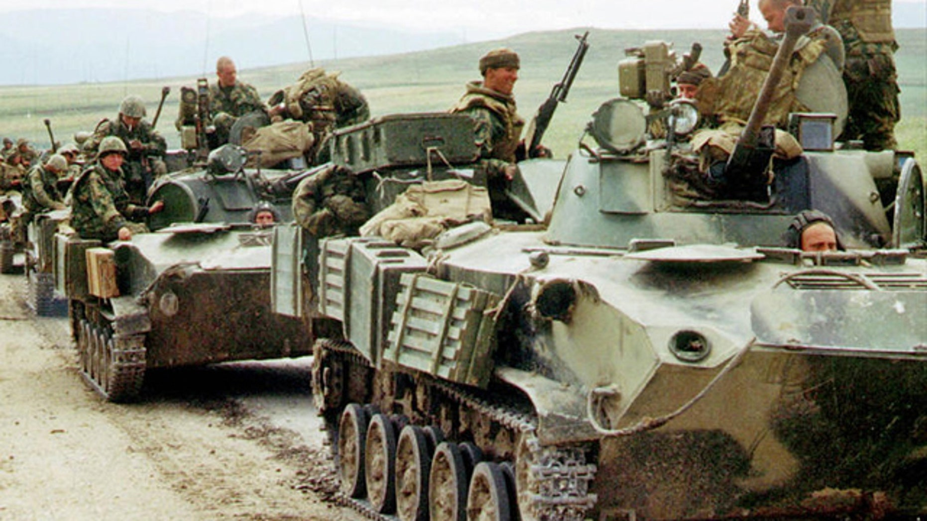 File: Russian paratroopers atop armored personnel carriers.