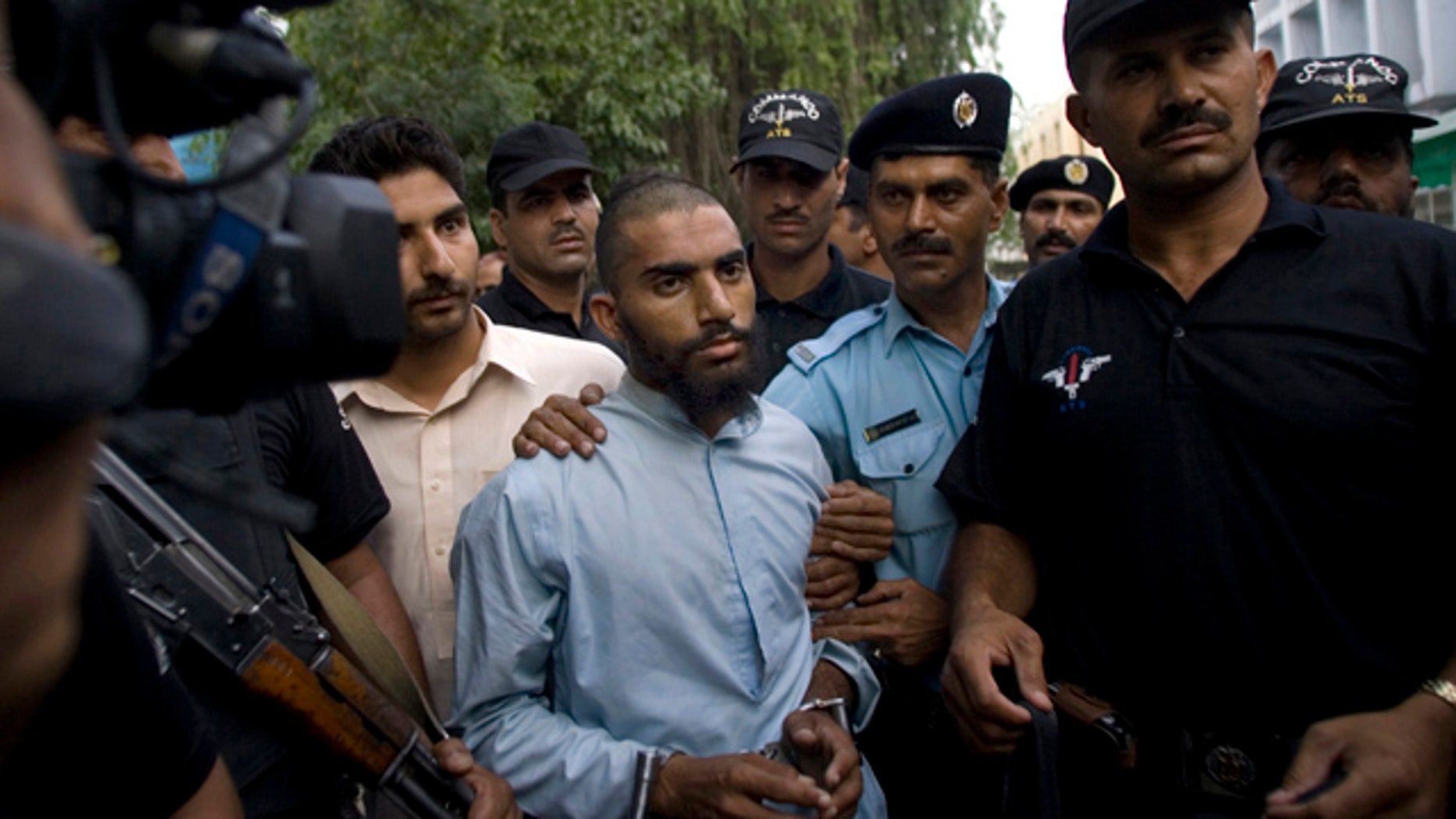 FILE - In this June 1, 2009 file photo, Pakistani police officers escort detained suspect militant Fida Ullah, center, who studied from radical Red Mosque in Islamabad, Pakistan. Pakistani authorities now believe a dangerous new militant group, out to avenge a deadly army assault on the mosque three years ago, has carried out several major bombings in the capital previously blamed on the Taliban. (AP Photo/Anjum Naveed, File)