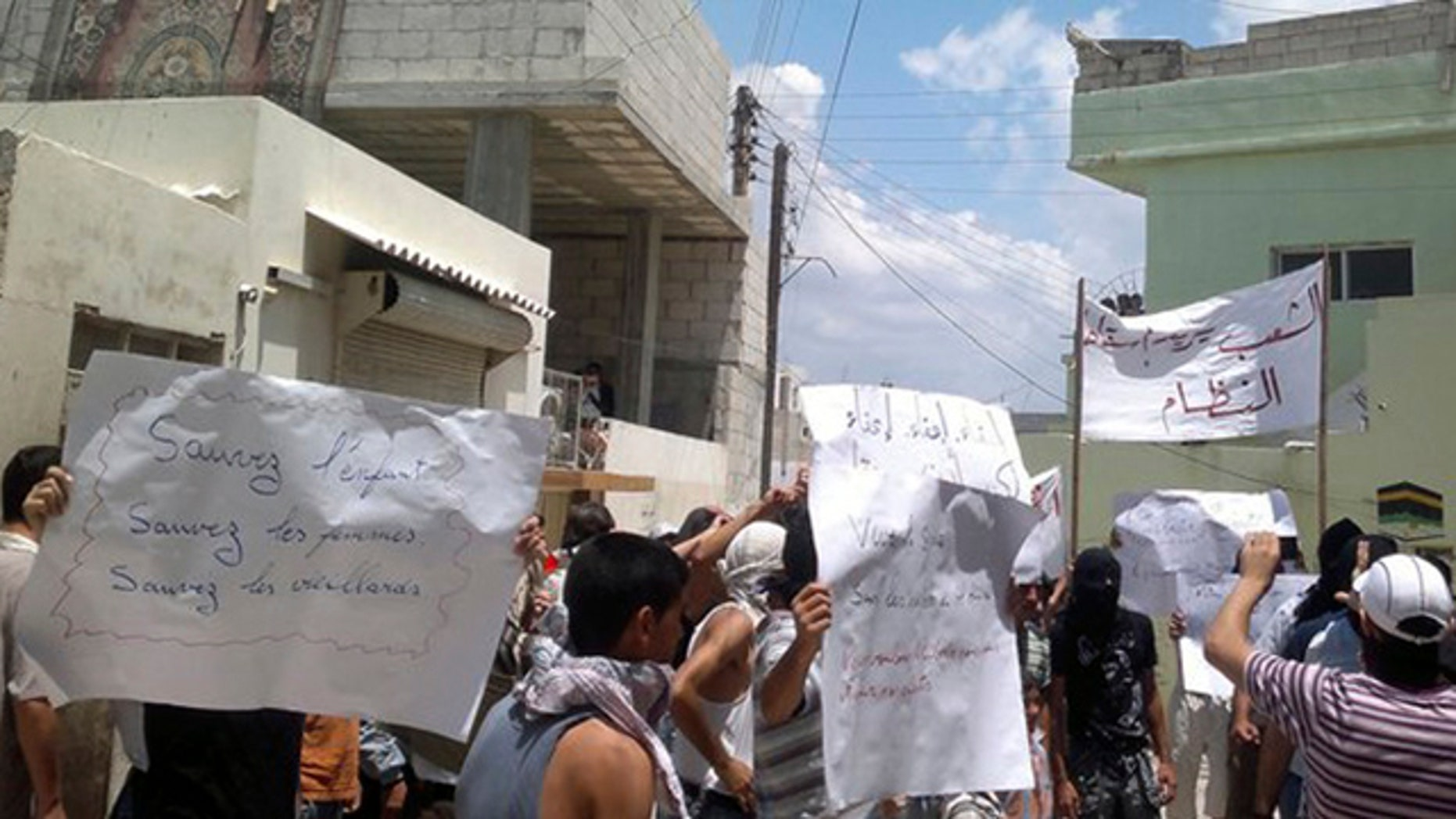 June 30: In this citizen journalism image made on a mobile phone and provided by Shaam News Network, anti-Syrian President Bashar Assad protesters hold banners during a demonstration against the Syrian regime in the coastal city of Banias, Syria.