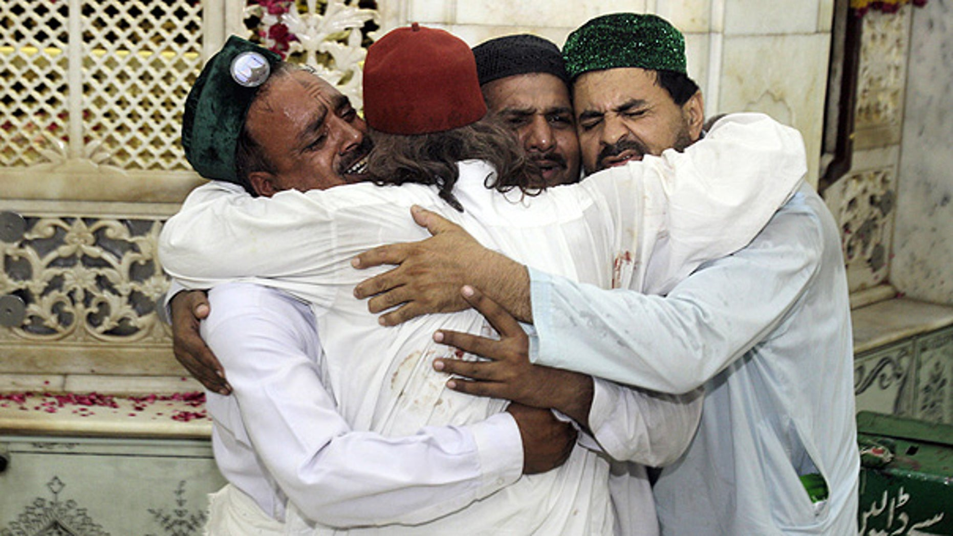 July 1: Family members of victims comfort one another after bombers attacked a popular Muslim shrine in Lahore, Pakistan.