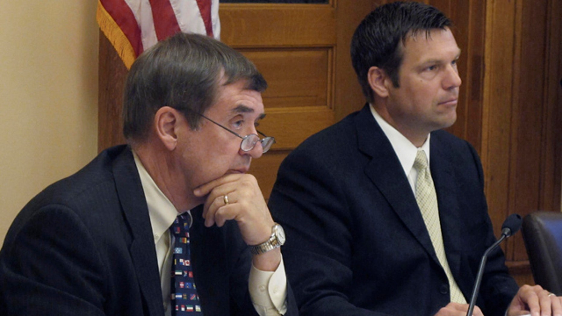 June 30: Kansas Secretary of Administration Dennis Taylor, left, and Secretary of State Kris Kobach, right, listen to a presentation on new regulations for abortion clinics at the Statehouse in Topeka, Kan.