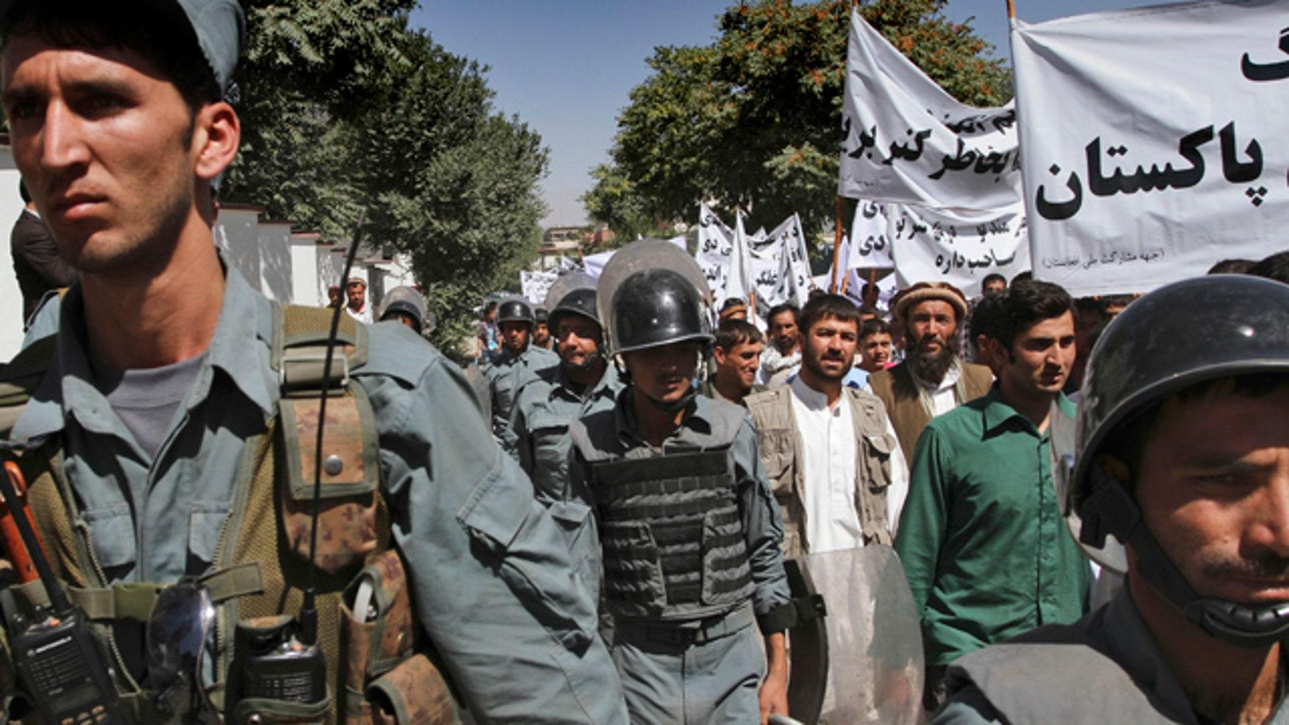 July 2: Afghan policemen escort protestors during an anti-Pakistan demonstration in Kabul, Afghanistan.