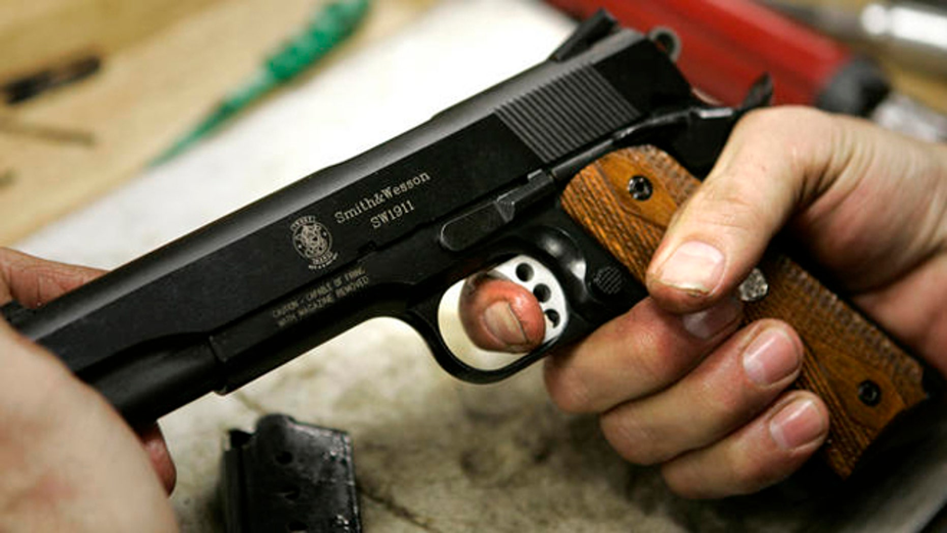 FILE: Undated: A model 1911 pistol is held in the hands of an assembler at the Smith & Wesson factory in Springfield, Mass.