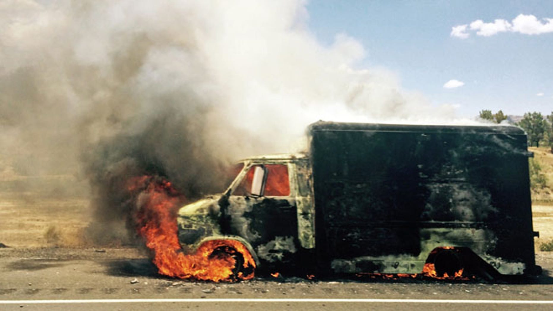 Kuly 2, 2015: In this photo provided by Jay Rutherford, smoke rises from a burning truck packed with fireworks after it exploded on Interstate 15 near Ivanpah, Calif., close to the Nevada state line.