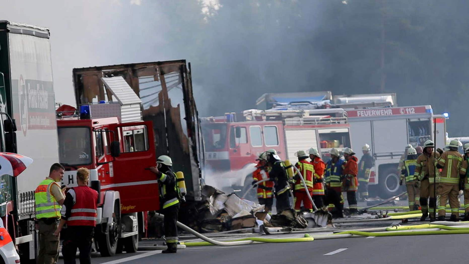 Rescue workers stand beside burnt-out coach on the motorway A9 near Muenchberg, southeastern Germany, Monday, July 3, 2017 after a bus crashed into a truck and caught fire.