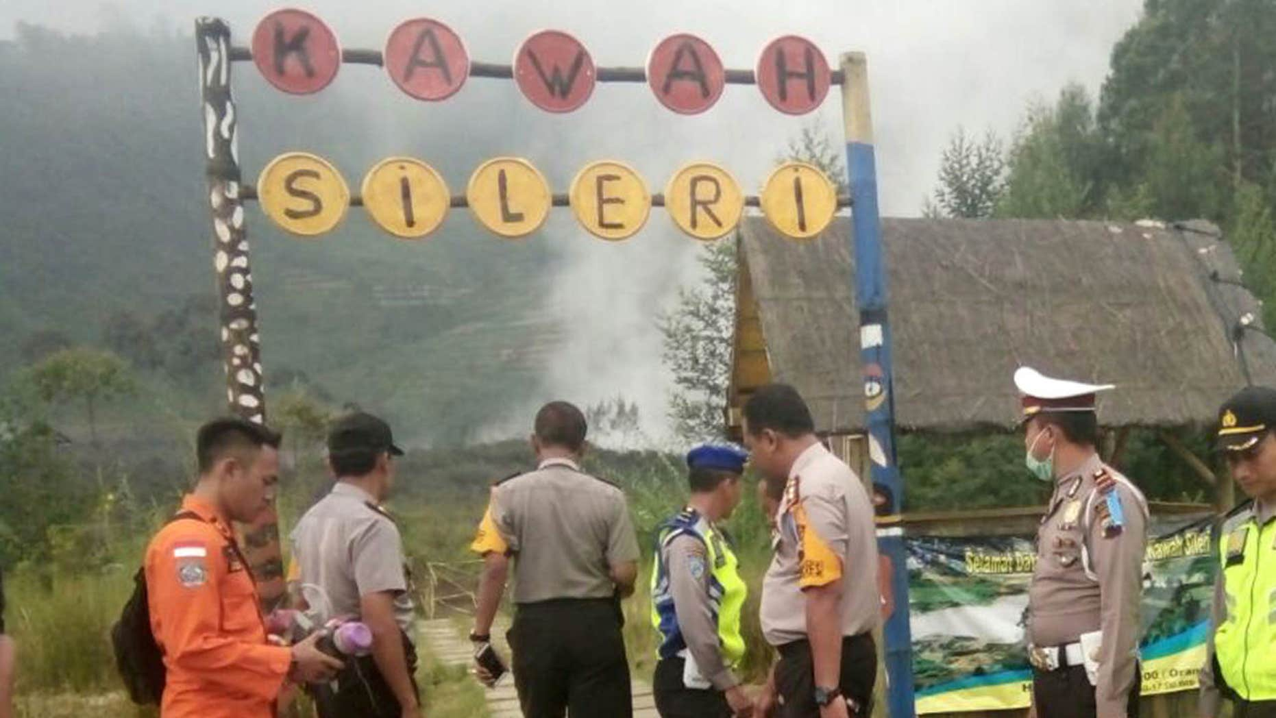July 2, 2017: Police officers and a rescuer stand at a path leading to Sileri Crater after it erupted in Dieng, Central Java, Indonesia.